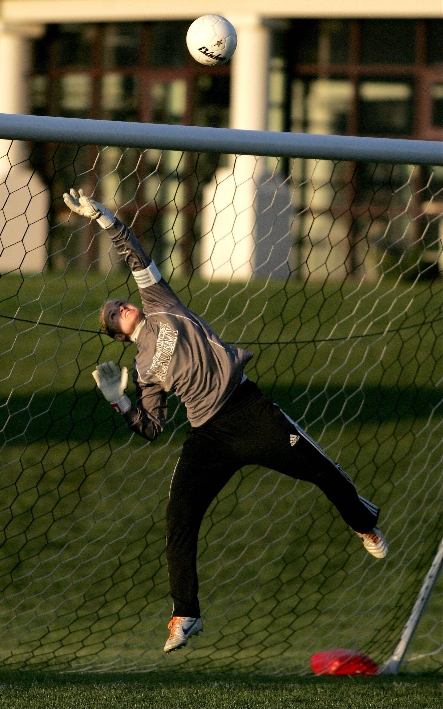 Kristen Morency of Wheaton Academy knocks the ball from the net in girls soccer action against Benet on Monday in West Chicago.
