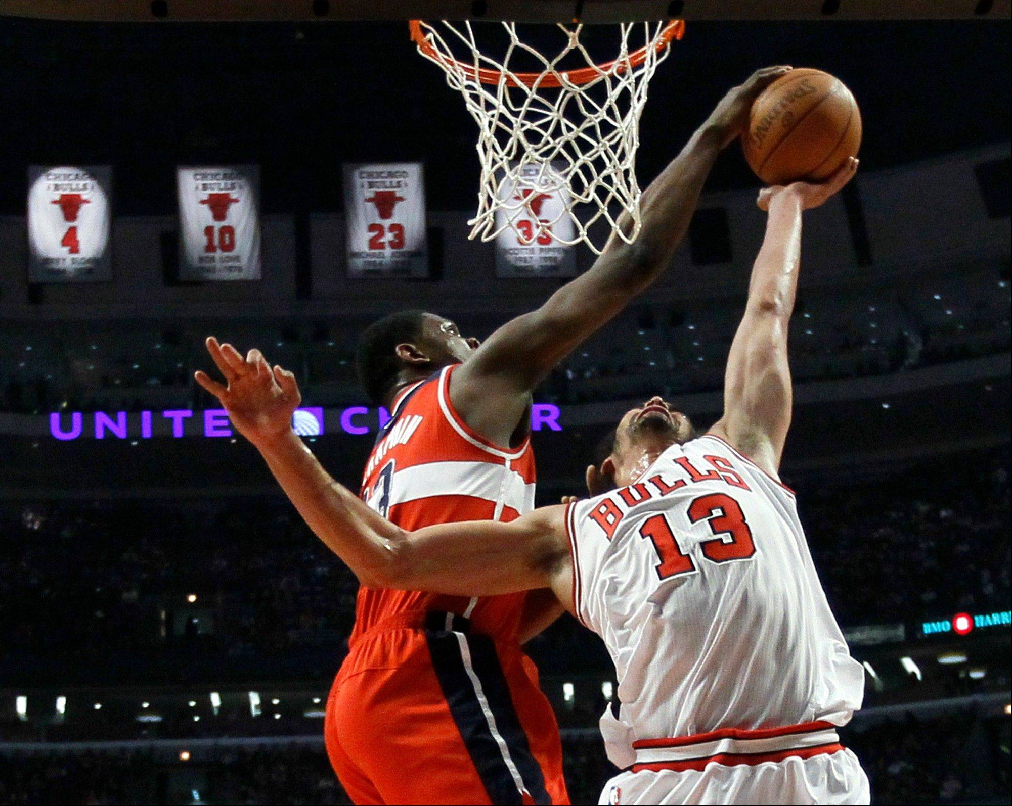 Washington Wizards forward Kevin Seraphin (13) blocks the shot of Chicago Bulls center Joakim Noah, during the first half of an NBA basketball game Monday, April 16, 2012, in Chicago.