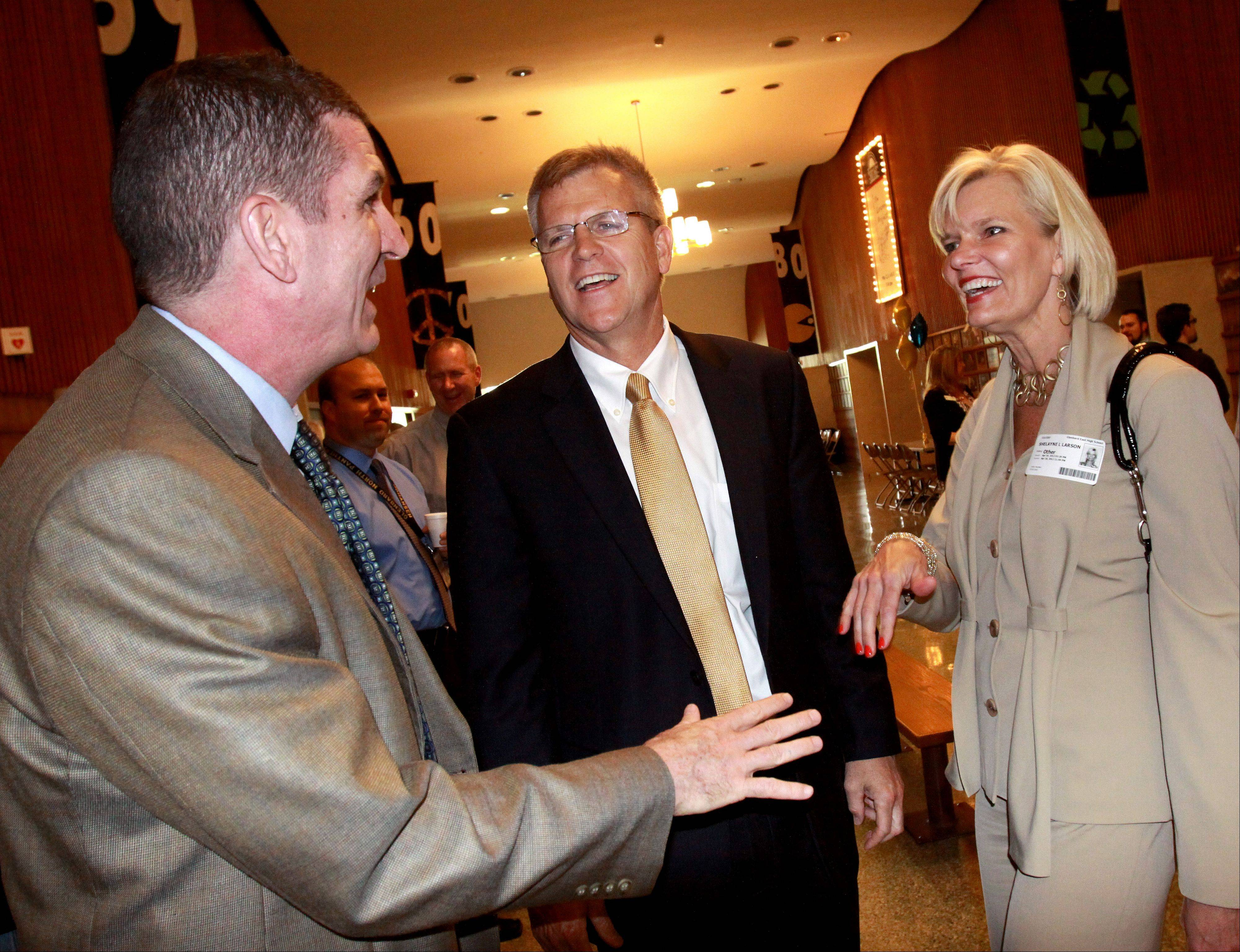 Peter Monaghan, left, assistant principal for student services at Glenbard West, greets new Glenbard District 87 Superintendent David Larson, with his wife Shelayne Larson, at a meet-and-greet reception Monday at Glenbard East in Lombard.