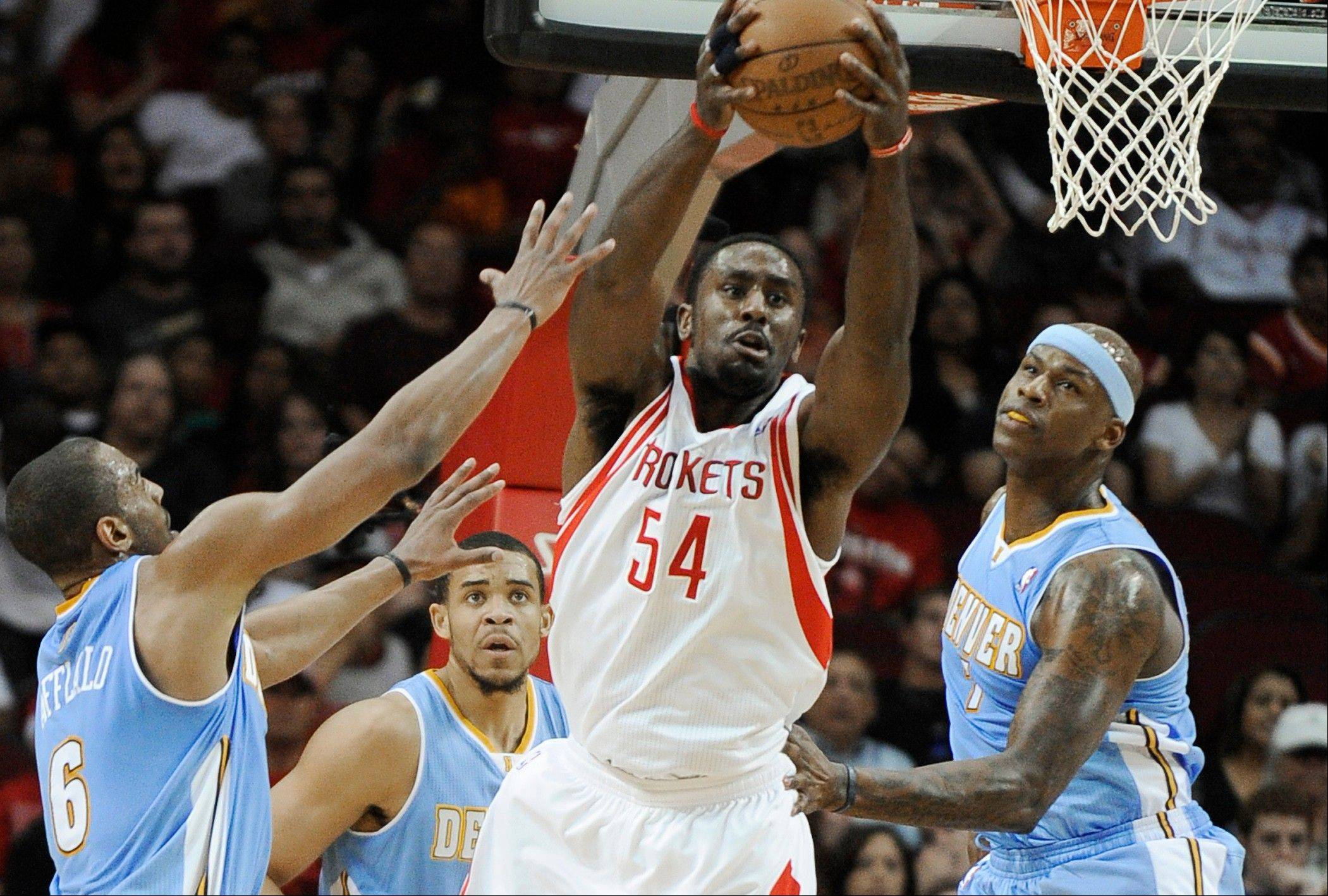The Rockets' Patrick Patterson grabs a rebound while surrounded by Denver's Arron Afflalo (6), JaVale McGee, center, and Al Harrington, right, in the first half Monday in Houston.
