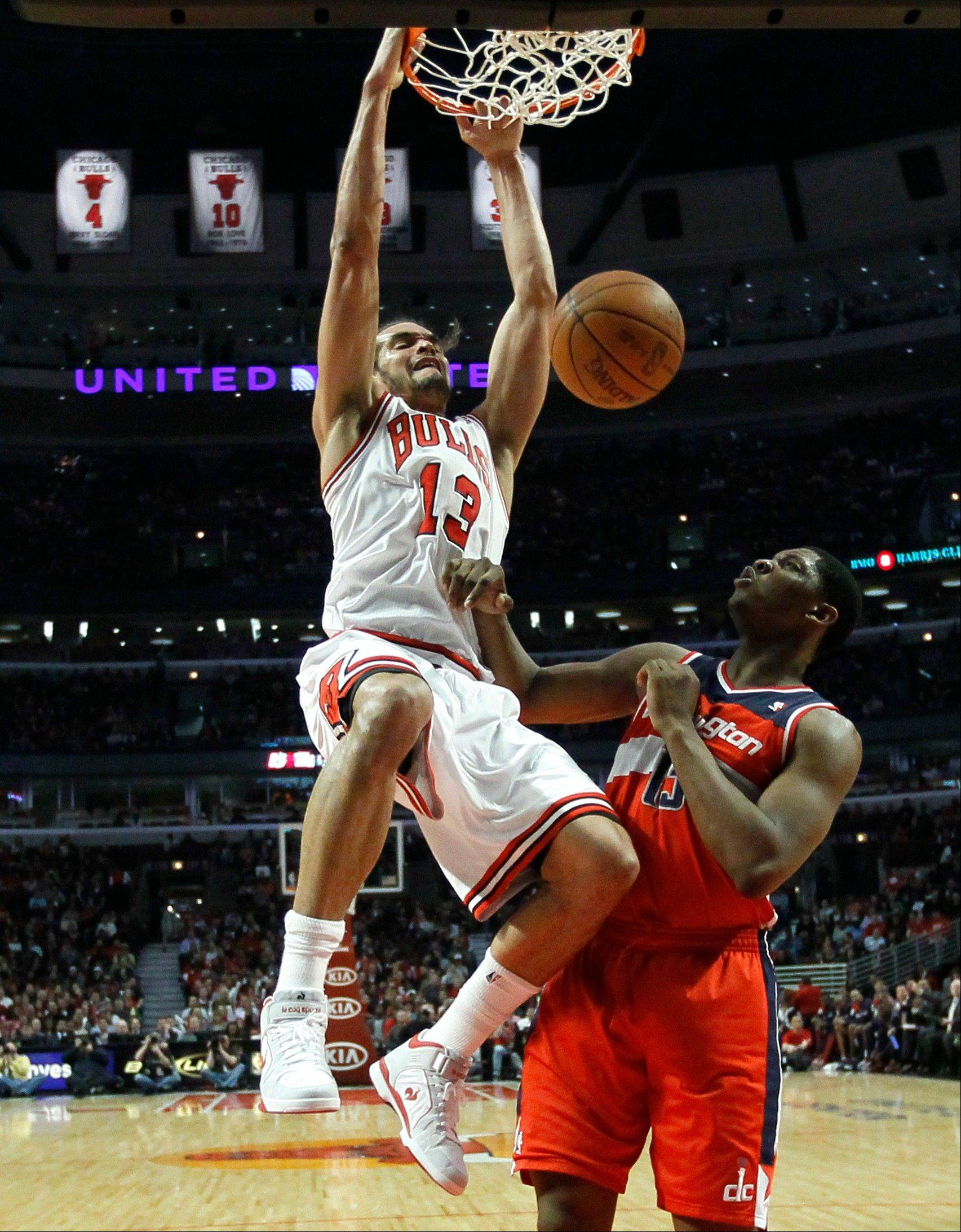 Joakim Noah (13) dunks over Washington Wizards forward Kevin Seraphin during the first half of Washington's victory Monday.