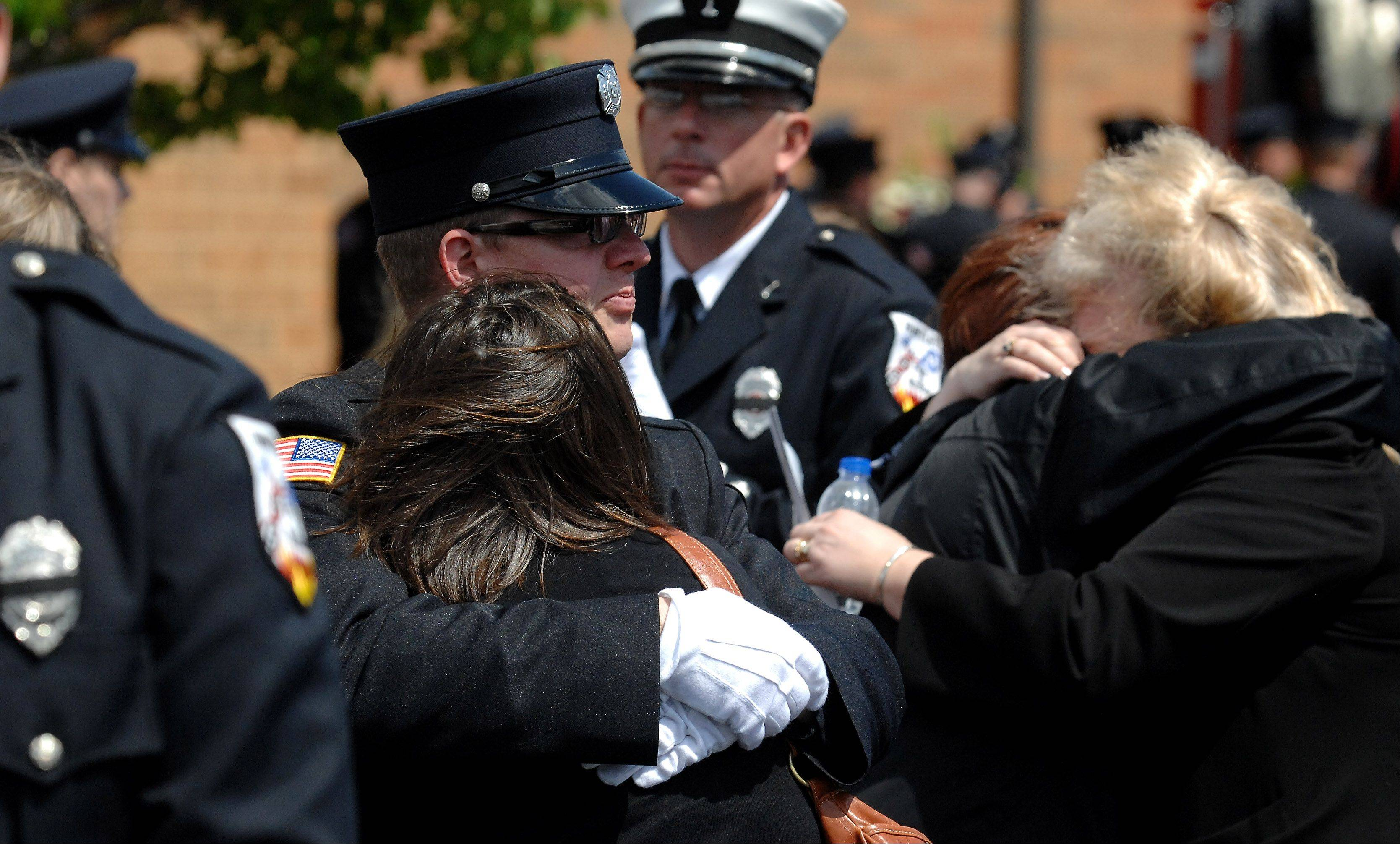 Rick West/rwest@dailyherald.com Mourners grieve after the funeral service for Huntley Fire Capt. John Winkelman at St. John's Lutheran Church in Union. Winkelman was killed in a motorcycle accident last week in Crystal Lake and because he was killed on duty, he received full firefighters honors during his service and burial.