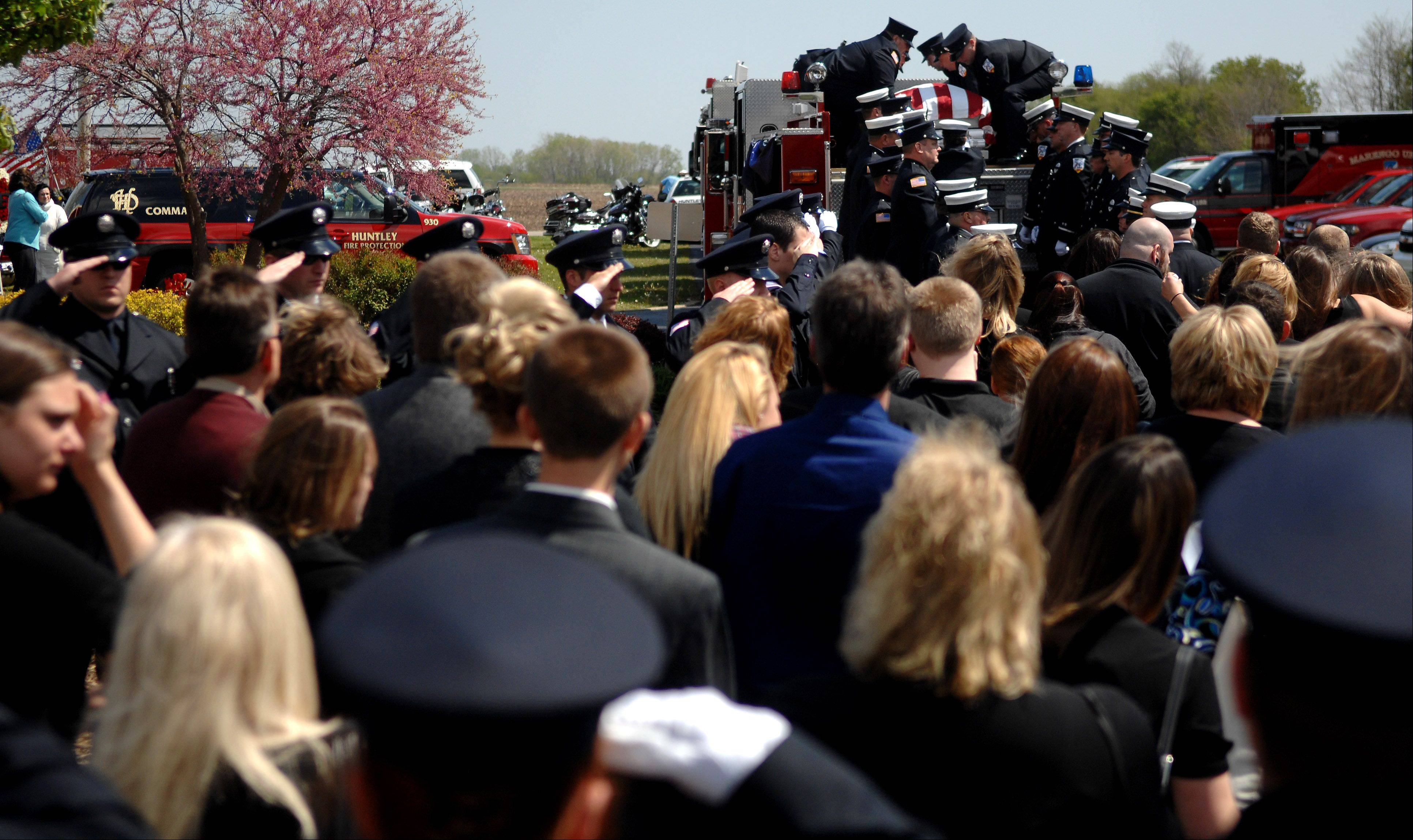 Mourners watch while firefighters secure the casket carrying Capt. John Winkelman onto Huntley Fire Engine #941 at St. John's Lutheran Church in Union. Winkelman, 54, lived in nearby Marengo and was killed last week in a motorcycle accident while on duty. More than 450 turned out for his funeral and five people eulogized him.