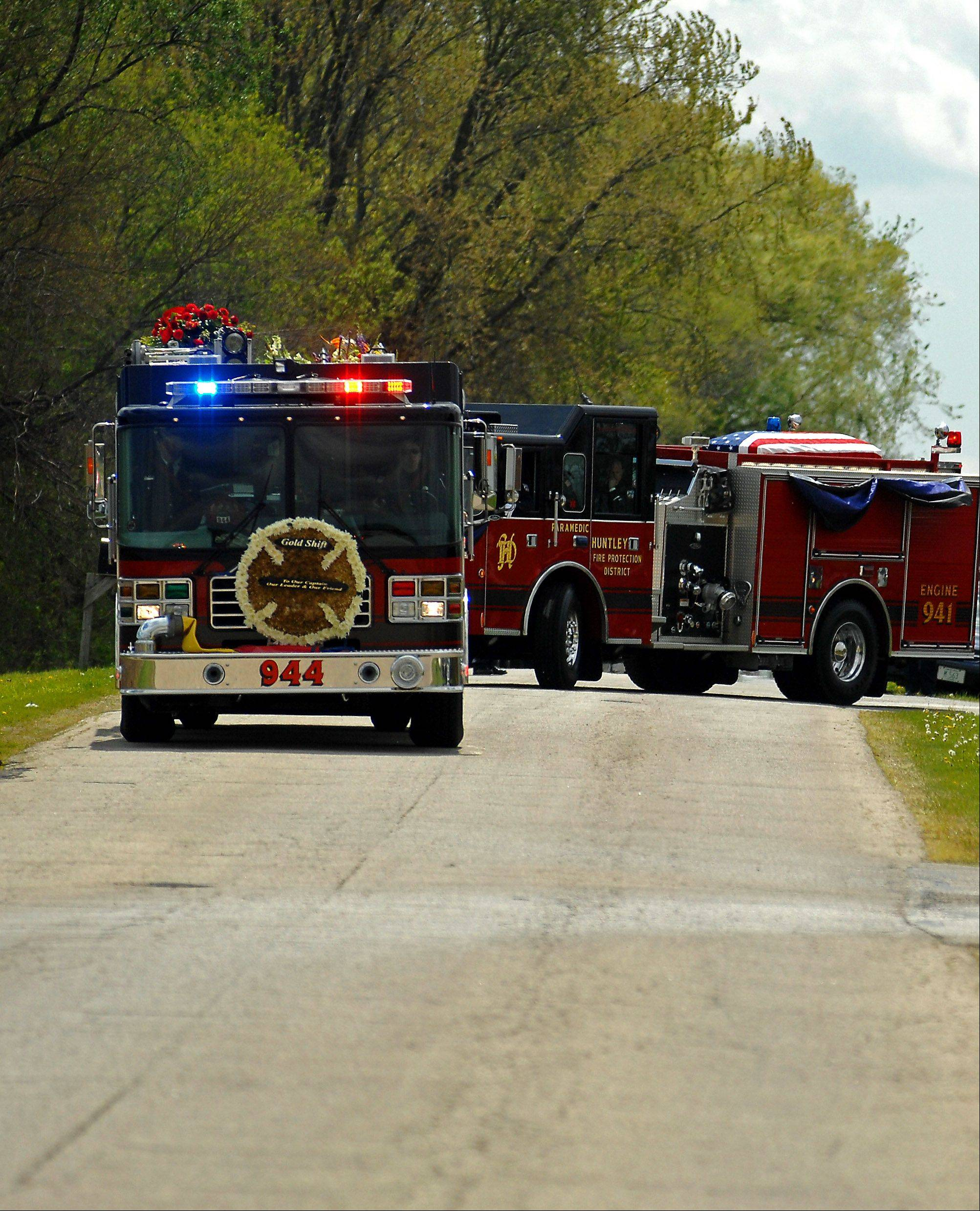 Fire engines from the Huntley Fire Protection District leave St. John's Lutheran Church in Union as part of the procession toward Marengo City Cemetery for the burial of Huntley Fire Capt. John Winkelman Wednesday. The engines silently flashed their lights in his honor.