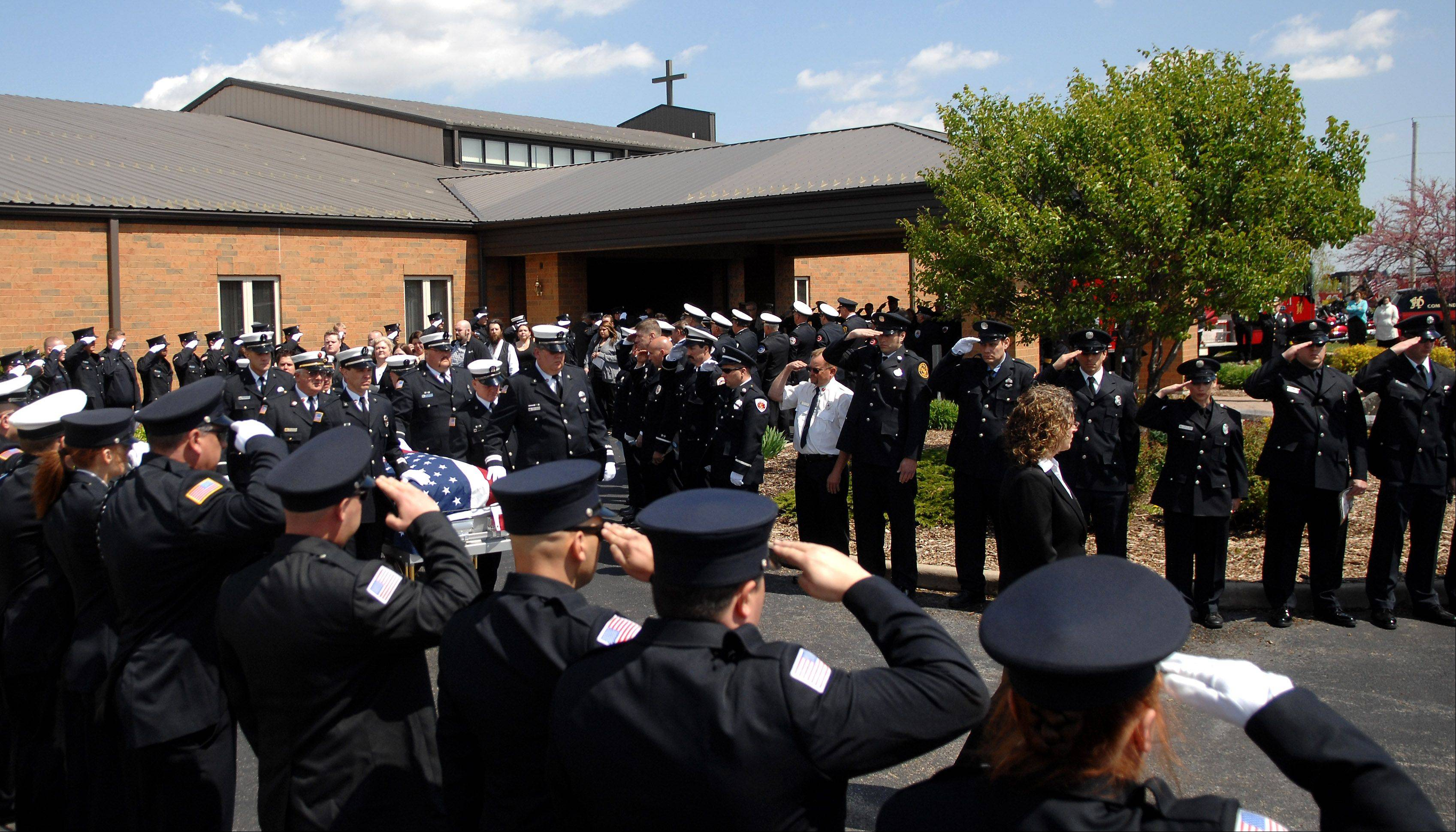Firefighters from around the region salute as the casket carrying Huntley Fire Capt. John Winkelman is brought out of St. John's Lutheran Church after his funeral in Union Wednesday. Winkelman was killed on duty in a motorcycle accident last week in Crystal Lake, while on his way home from a committee meeting.