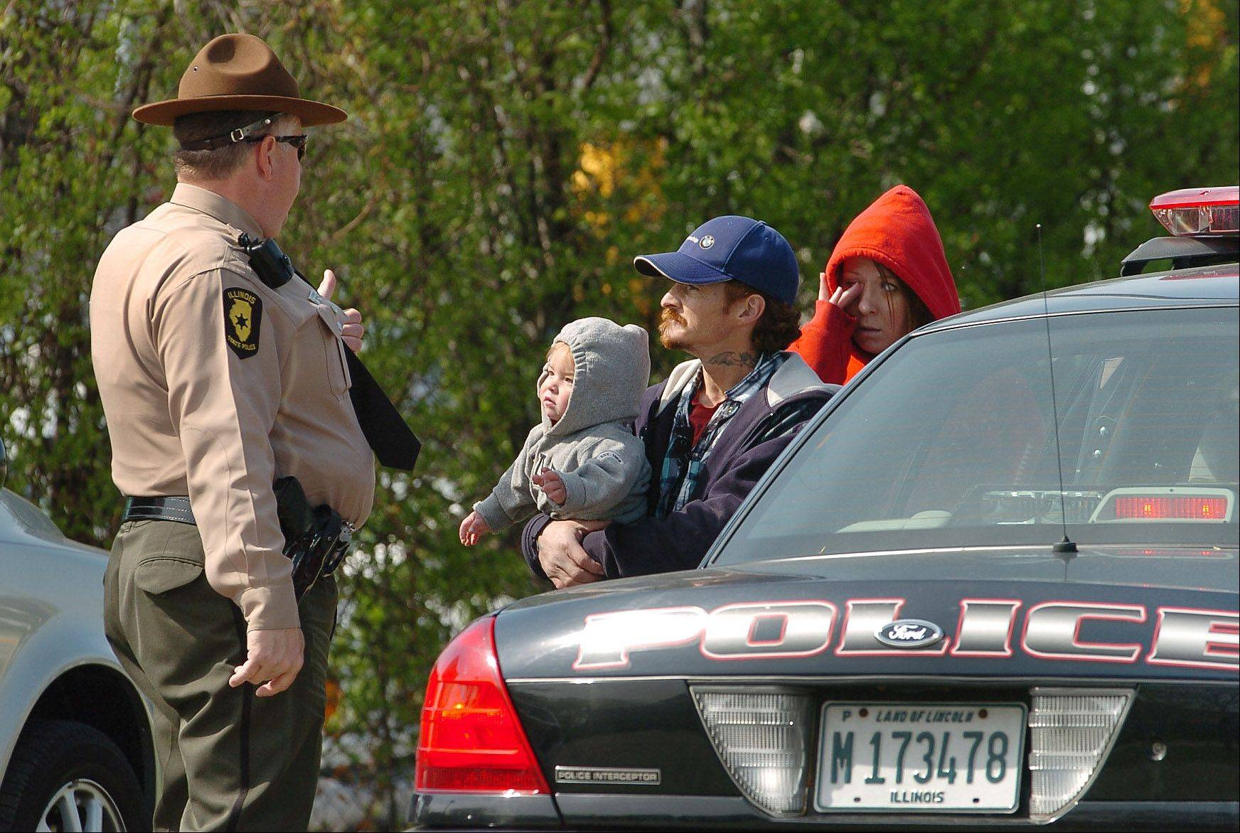 Bob Chwedyk/bchwedyk@dailyherald.comJoey and April Giancaspro, seeking donations with their 1-year-old son, Gavin, were warned Wednesday by a state trooper to leave the corner for the safety of the child.