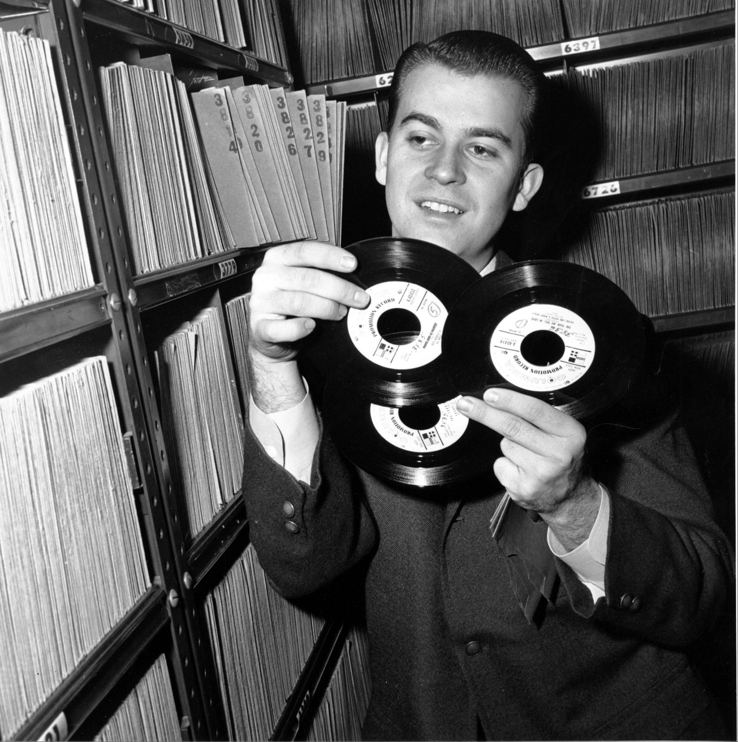 "In this Feb. 3, 1959 file photo, Dick Clark selects a record in his station library in Philadelphia. Clark, the television host who helped bring rock `n' roll into the mainstream on ""American Bandstand,"" died Wednesday, April 18, 2012 of a heart attack. He was 82."