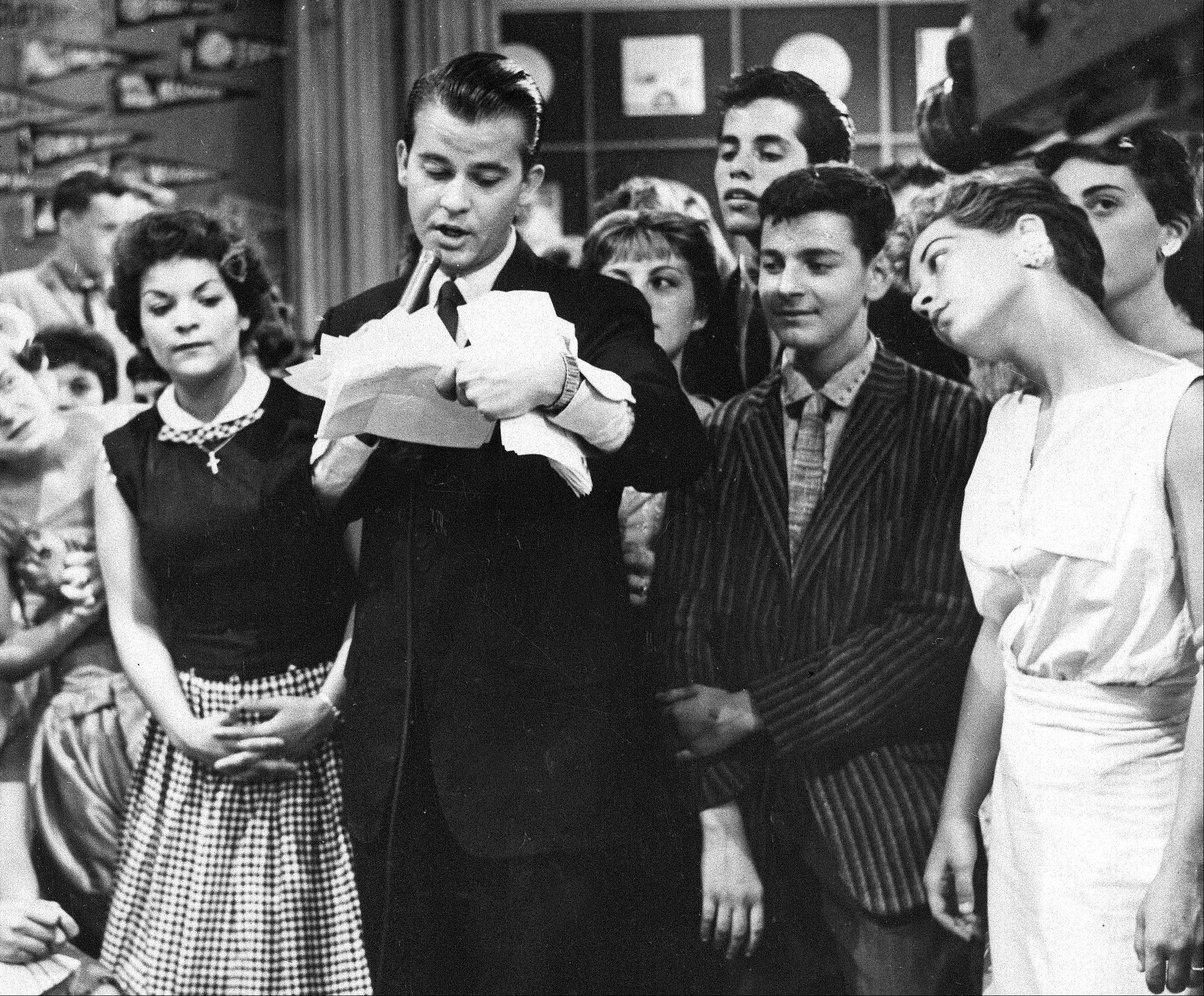 "In this 1957 file photo, Dick Clark is seen surrounded by fans during a television broadcast of ""American Bandstand."""