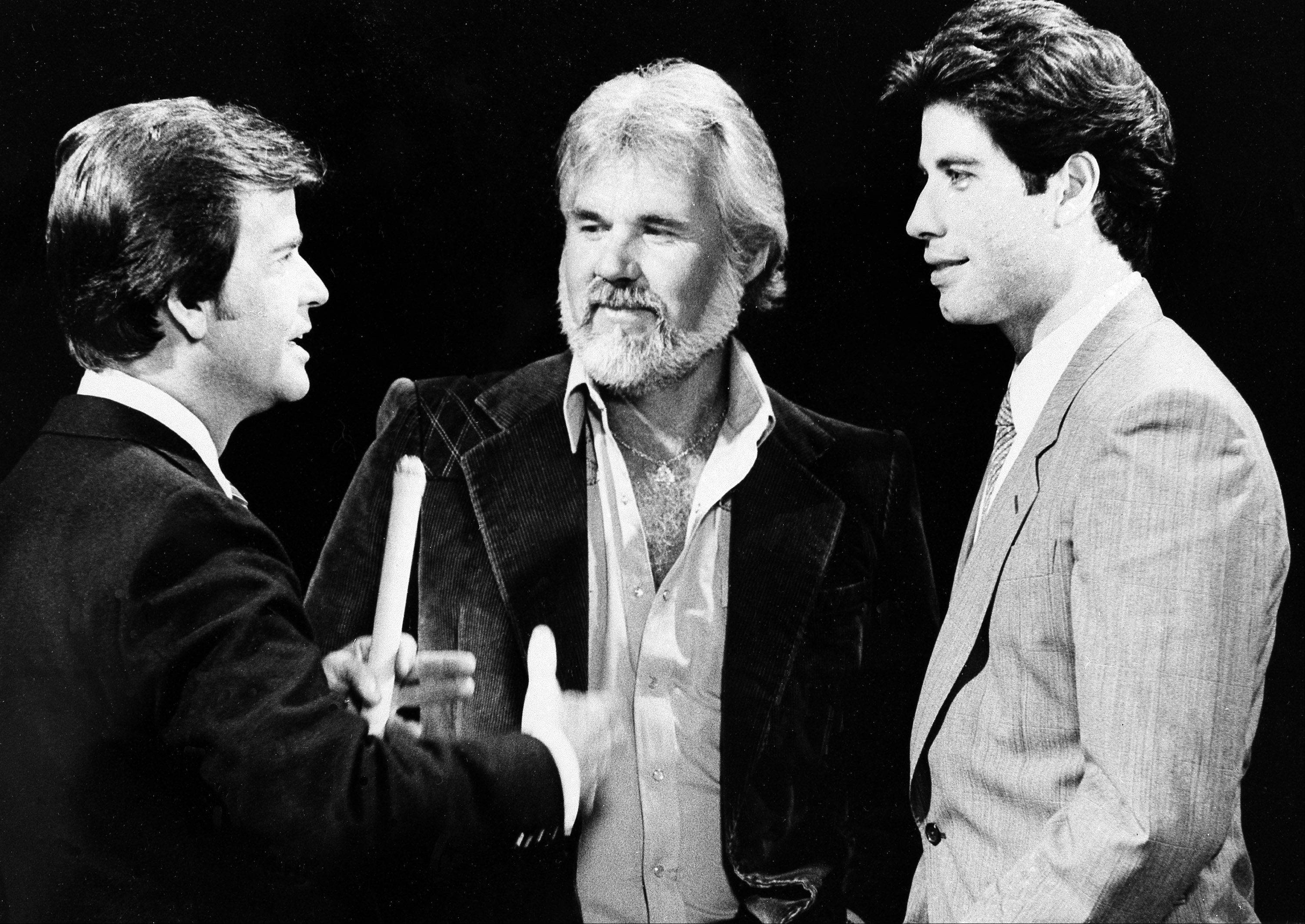 """American Bandstand"" host Dick Clark, left, reminisces with Kenny Rogers, center, and John Travolta about their early music careers during taping recently of "" American Bandstand's 30th Anniversary Special."" October 27, 1981."