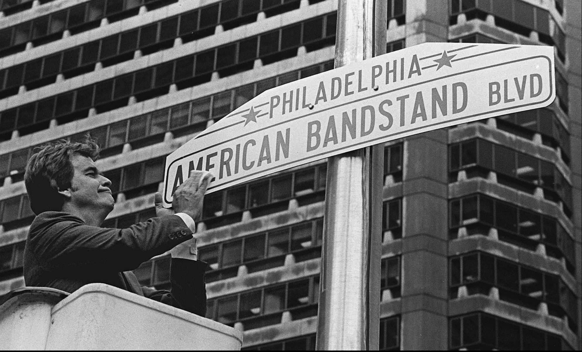 Television personality Dick Clark shines a new sign that changes a portion of Philadelphia's Market Street to American Bandstand Boulevard on October 27, 1981, to recognize the 30th anniversary of the popular dance program that originated in Philadelphia.
