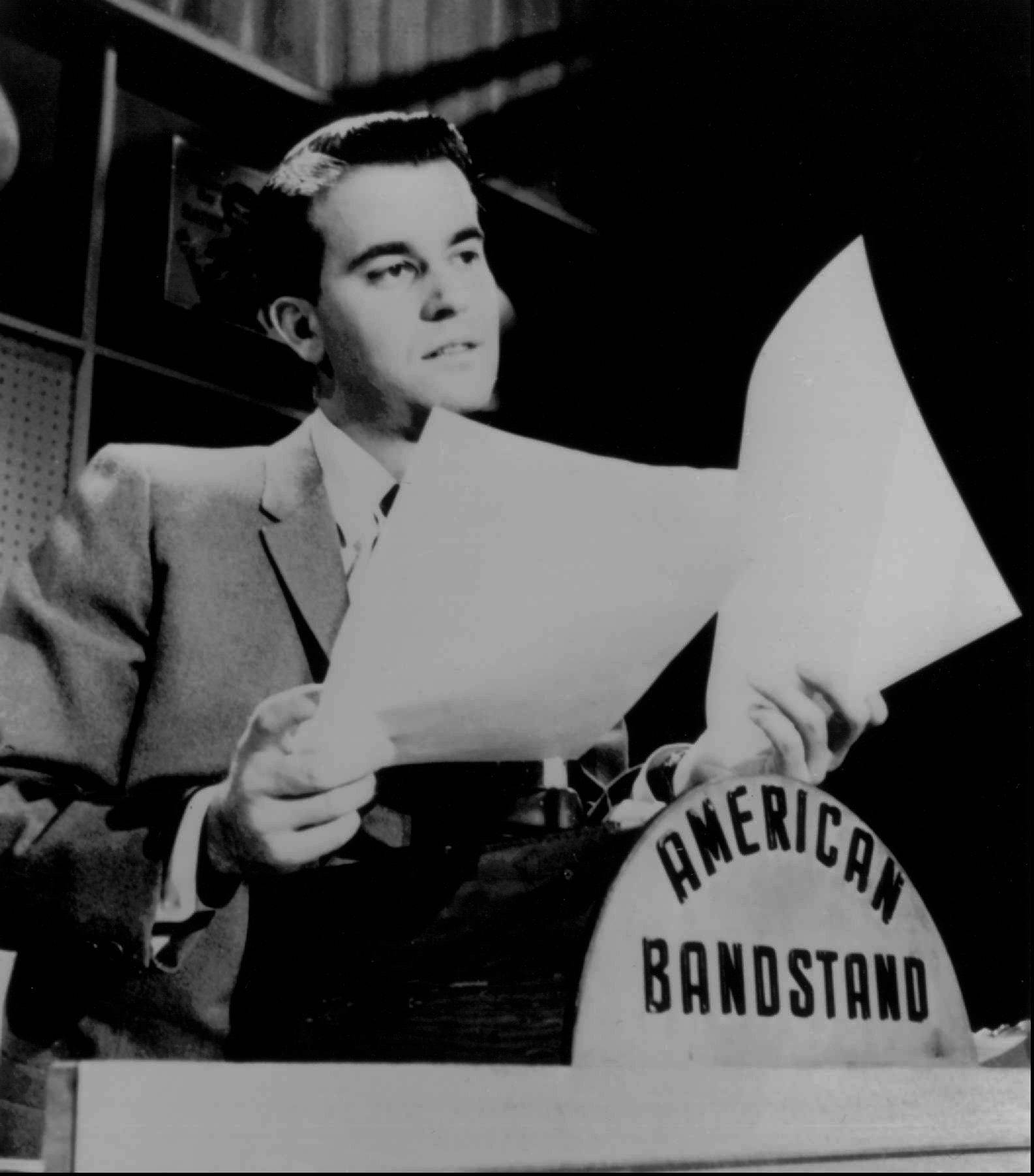 Disc jockey television personality Dick Clark looks over some papers during an American Bandstand show in Philadelphia in this undated photo.
