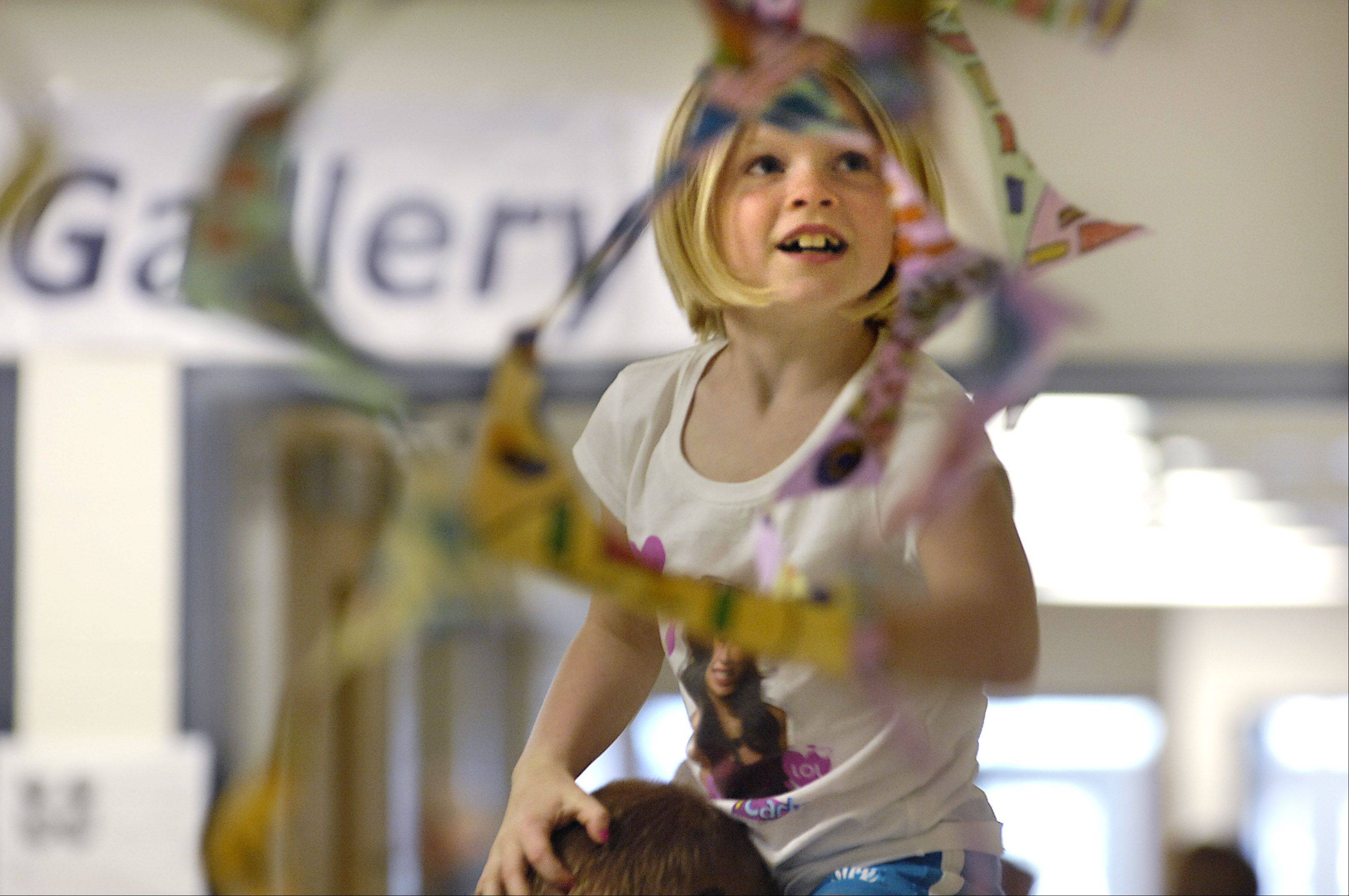 Second-grader Brianna Vestal sits on her dad Don's shoulders to get eye level with her class artwork, a spinner hanging from the Kaneland High School ceiling during a previous Kaneland Community Fine Arts Festival. They are from Sugar Grove.