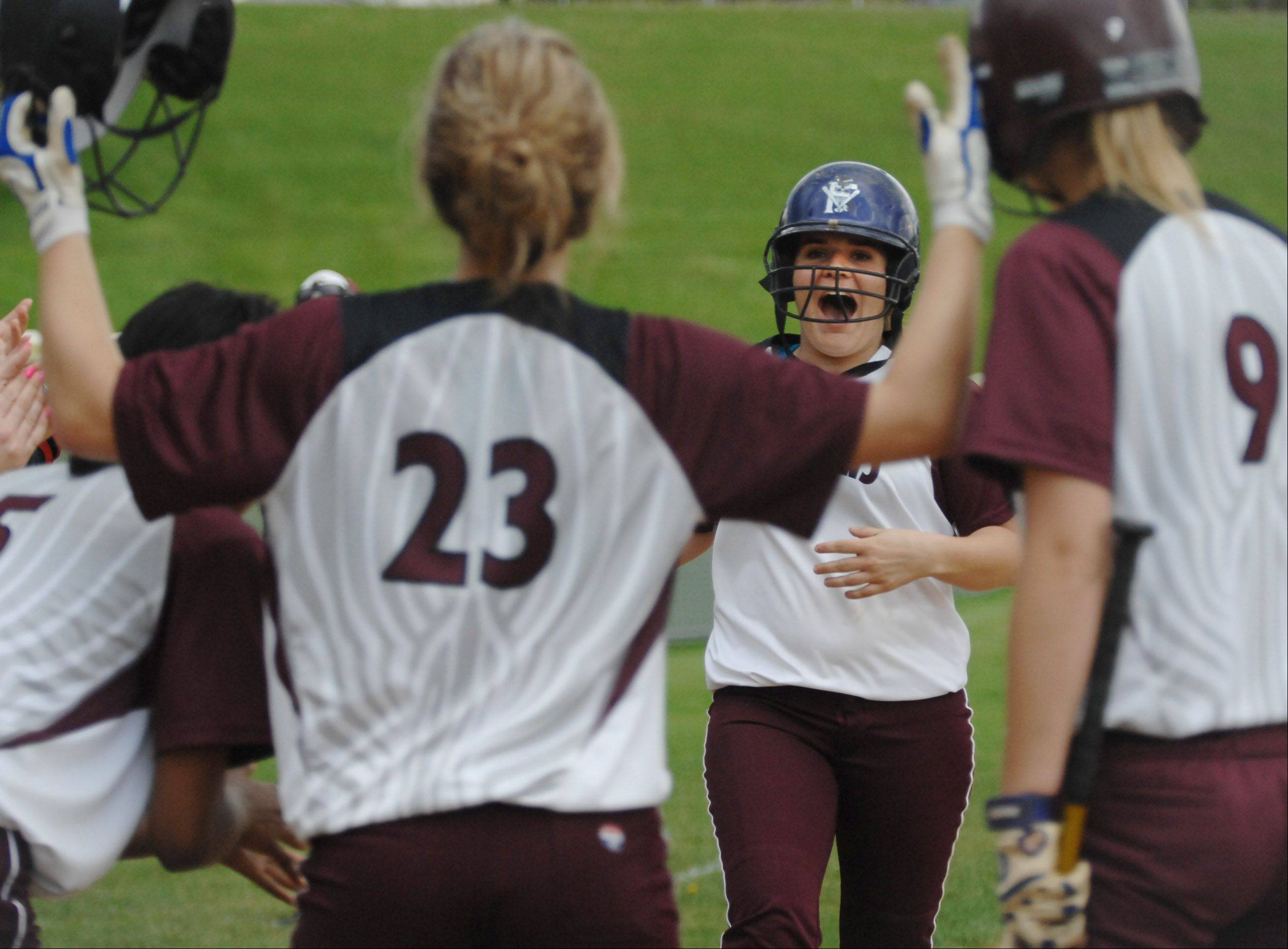 With winning pitcher Hannah Perryman (23) leading the welcoming party, Elgin sophomore Anna Eckholm celebrates as she approaches the plate after hitting a home run in the bottom of the sixth inning against Batavia Wednesday in Elgin. It was the only run of the game.