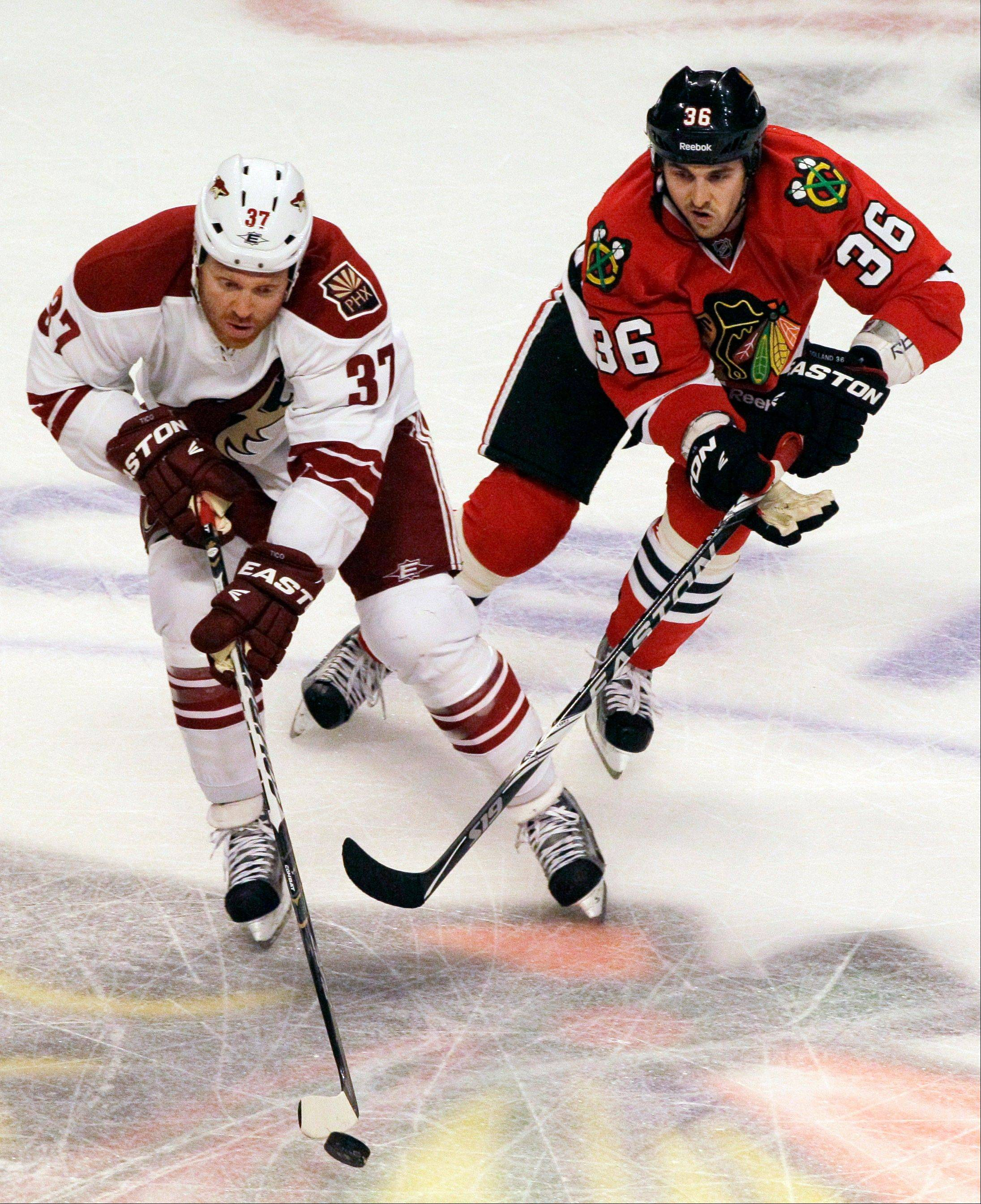 Phoenix Coyotes' Raffi Torres (37) controls the puck against Chicago Blackhawks' Dave Bolland (36) during the third period of Game 3 of an NHL hockey Stanley Cup first-round playoff series in Chicago, Tuesday, April 17, 2012. The Coyotes won 3-2.