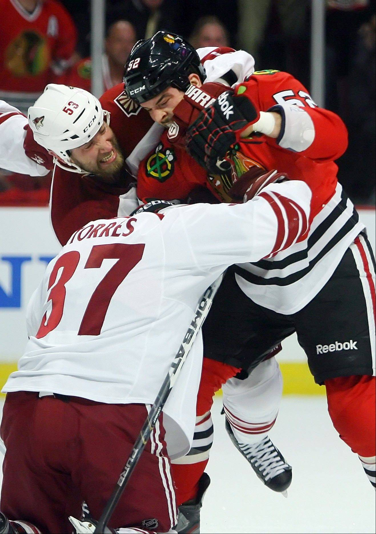 Blackhawks left wing Brandon Bollig goes after Phoenix Coyotes left wing Raffi Torres during Game 3 of the Western Conference quarterfinals Tuesday at the United Center. Torres has been suspended indefinitely for his hit on Marian Hossa.