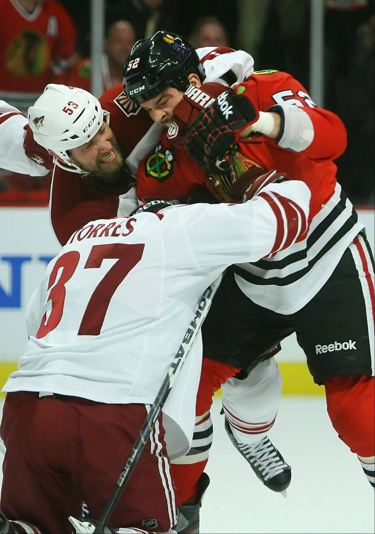 Chicago Blackhawks' left wing Brandon Bollig goes after Phoenix Coyotes left wing Raffi Torres .