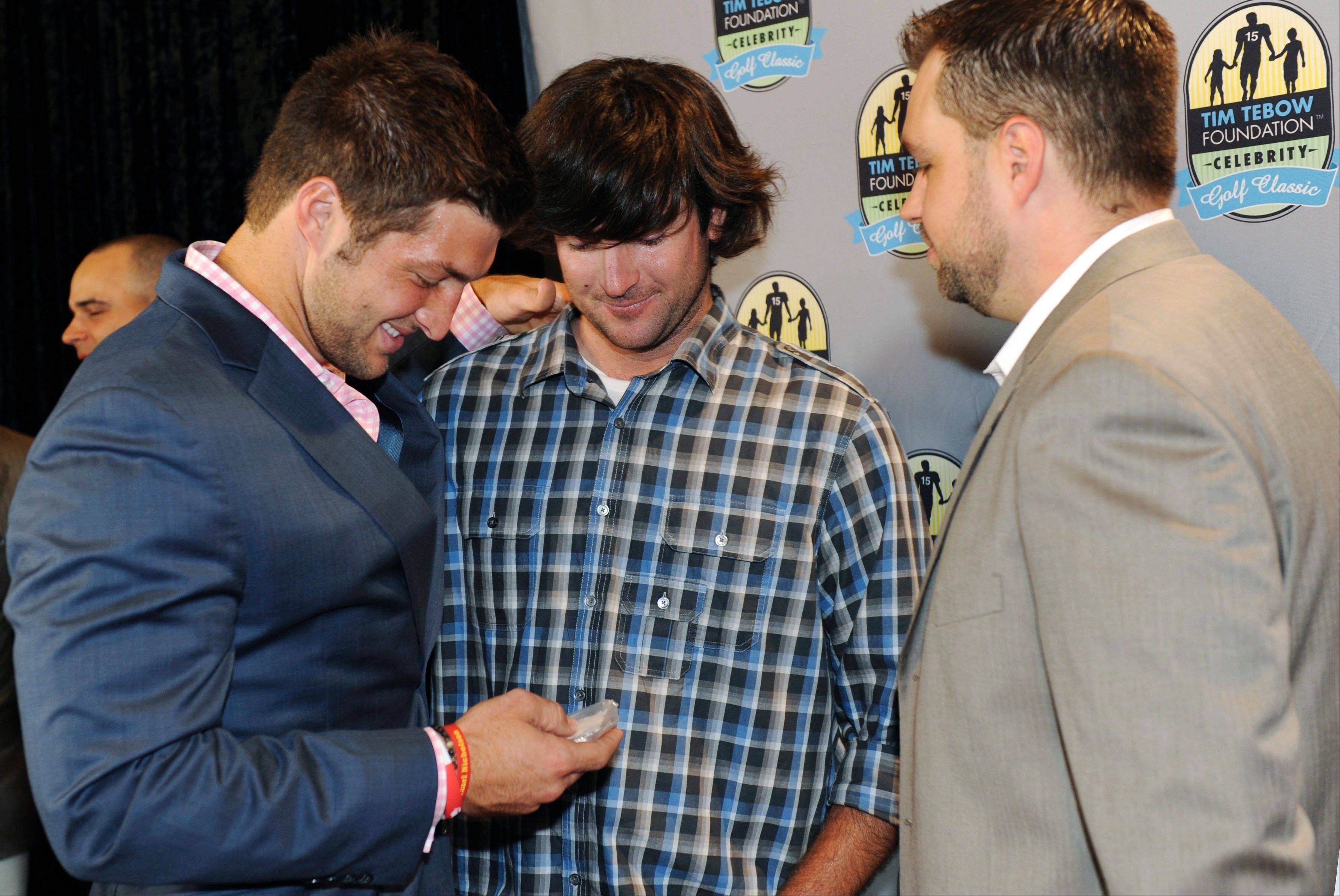 Masters golf champ Bubba Watson, center, presents New York Jets quarterback Tim Tebow, left, with his Masters golf tournament badge bearing number 15. Watson, who leads the Ryder Cup point standings, made the donation for the Tim Tebow Foundation Celebrity Golf Classic last Friday.