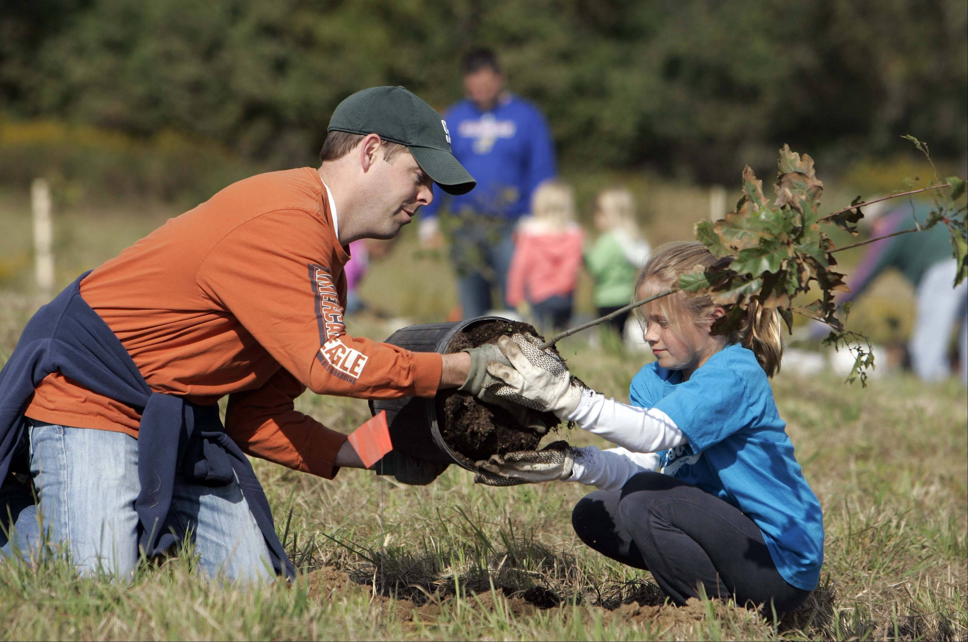 Derek, left, and Delaney Garden of Carpentersville help to plant an oak sapling at Schweitzer Woods Forest Preserve in West Dundee last year. Another tree planting day is slated for Saturday, April 21, in honor of Earth Day.