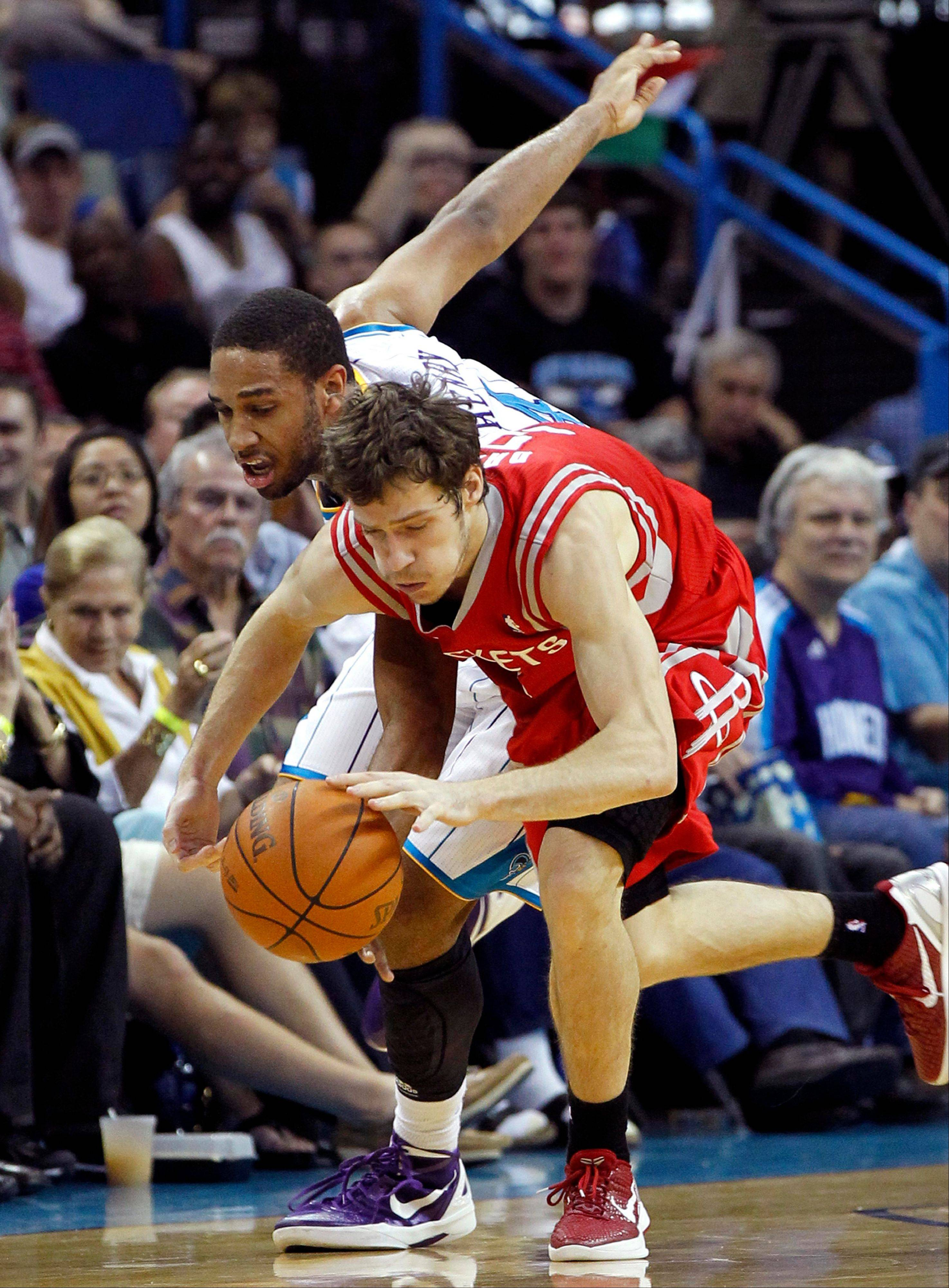 Houston Rockets point guard Goran Dragic battles for a loose ball with New Orleans Hornets shooting guard Xavier Henry in the second half Thursday in New Orleans.