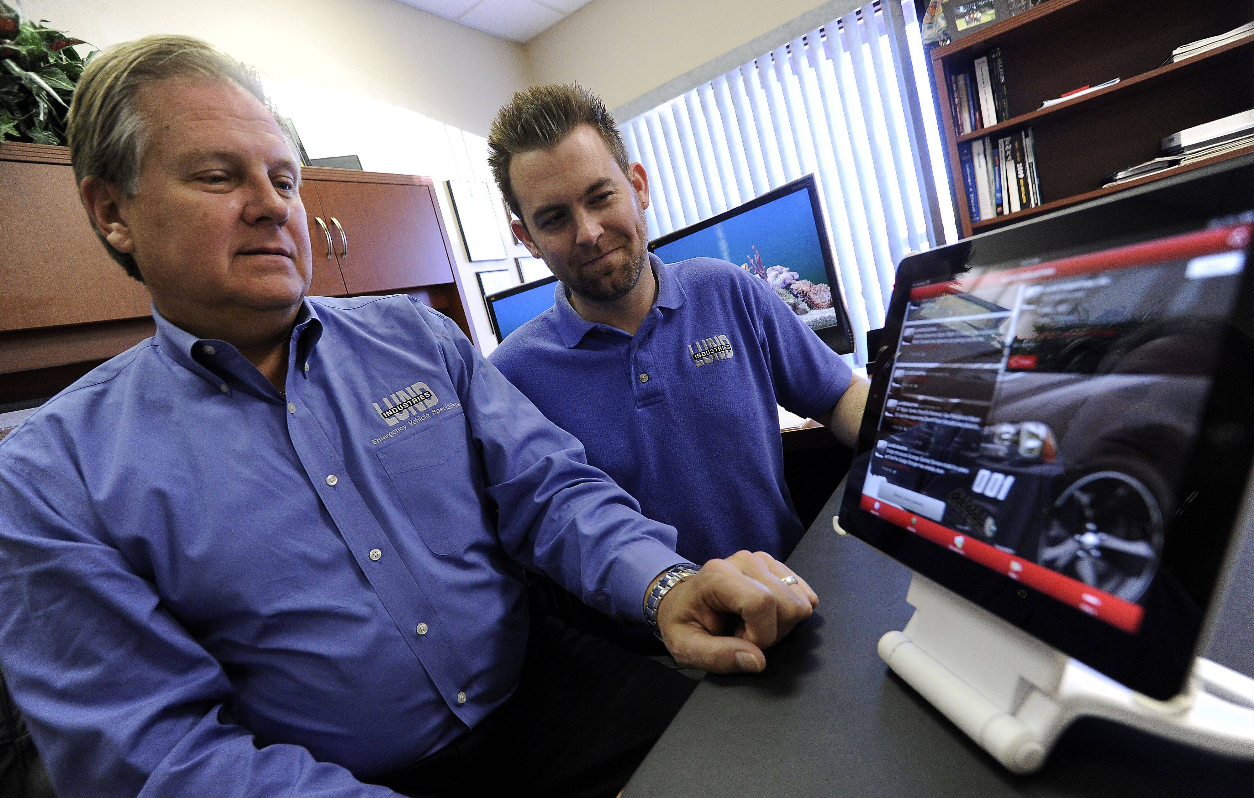 Michael Malec, left, of Lund Industries' sales department in Wheeling and Paul Lundberg, president of Lund, show off their app on an iPad.