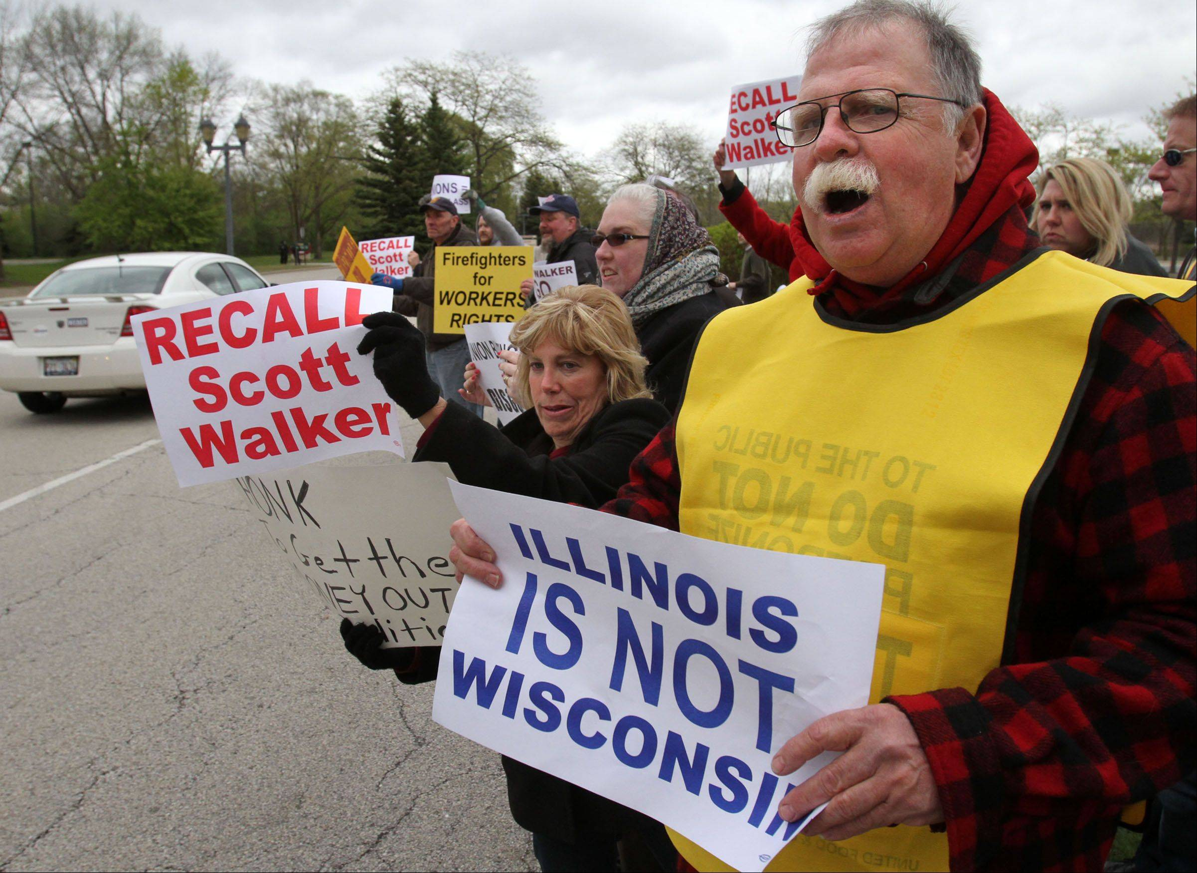 Peter Grant of Antioch with other protesters line the entrance area to the Lincolnshire Marriott Resort on Friday expecting Wisconsin Gov. Scott Walker to arrive to give the keynote address at the Lake County Republican Federation's annual spring dinner.