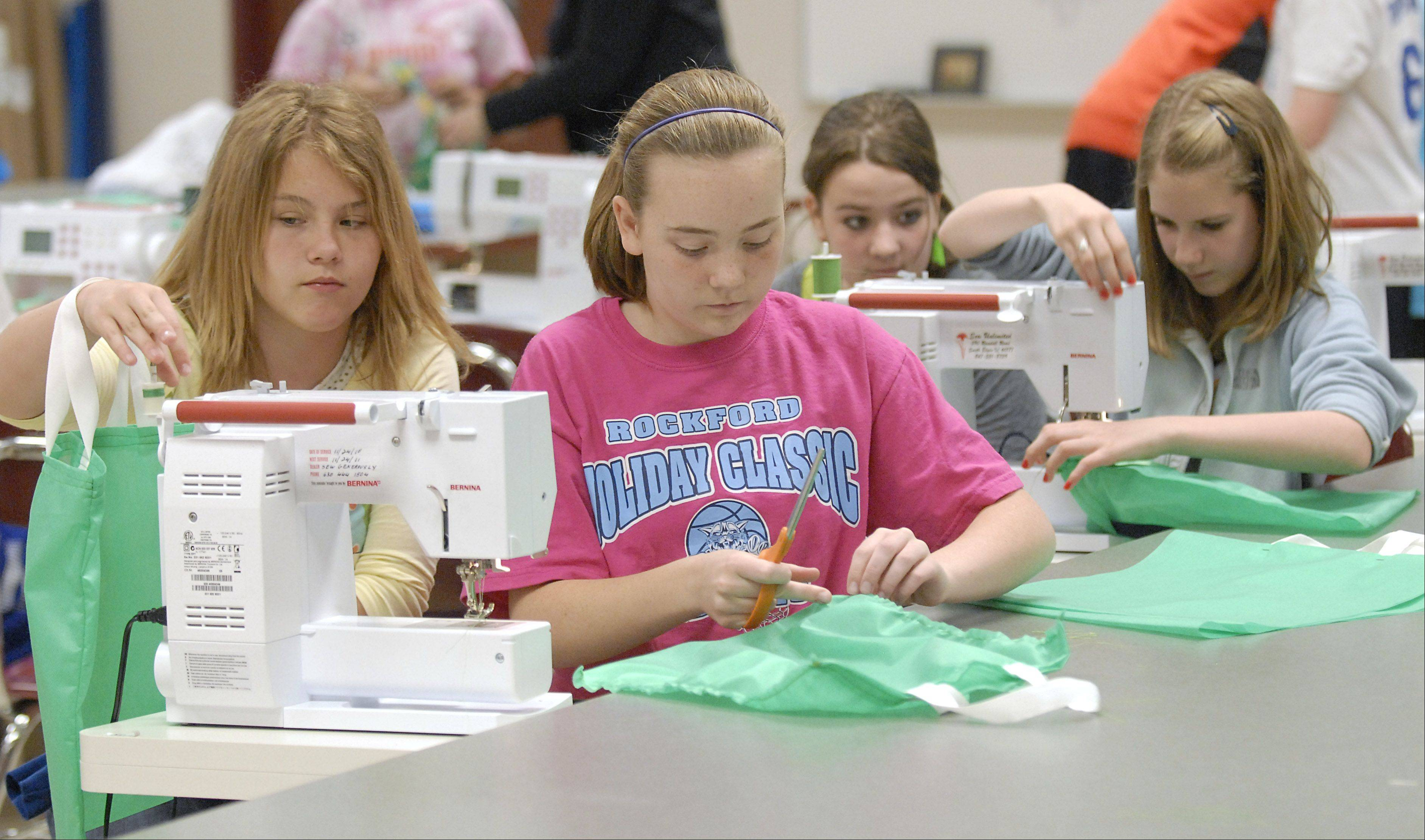 Seventh graders Jordan Witmer, left, and Jasey Segebrecht, both 13, finish sewing their reusable tote bag projects Friday at Geneva Middle School North. The seventh-grade class celebrated Earth Day by making the totes as well as crafts using recycled items.