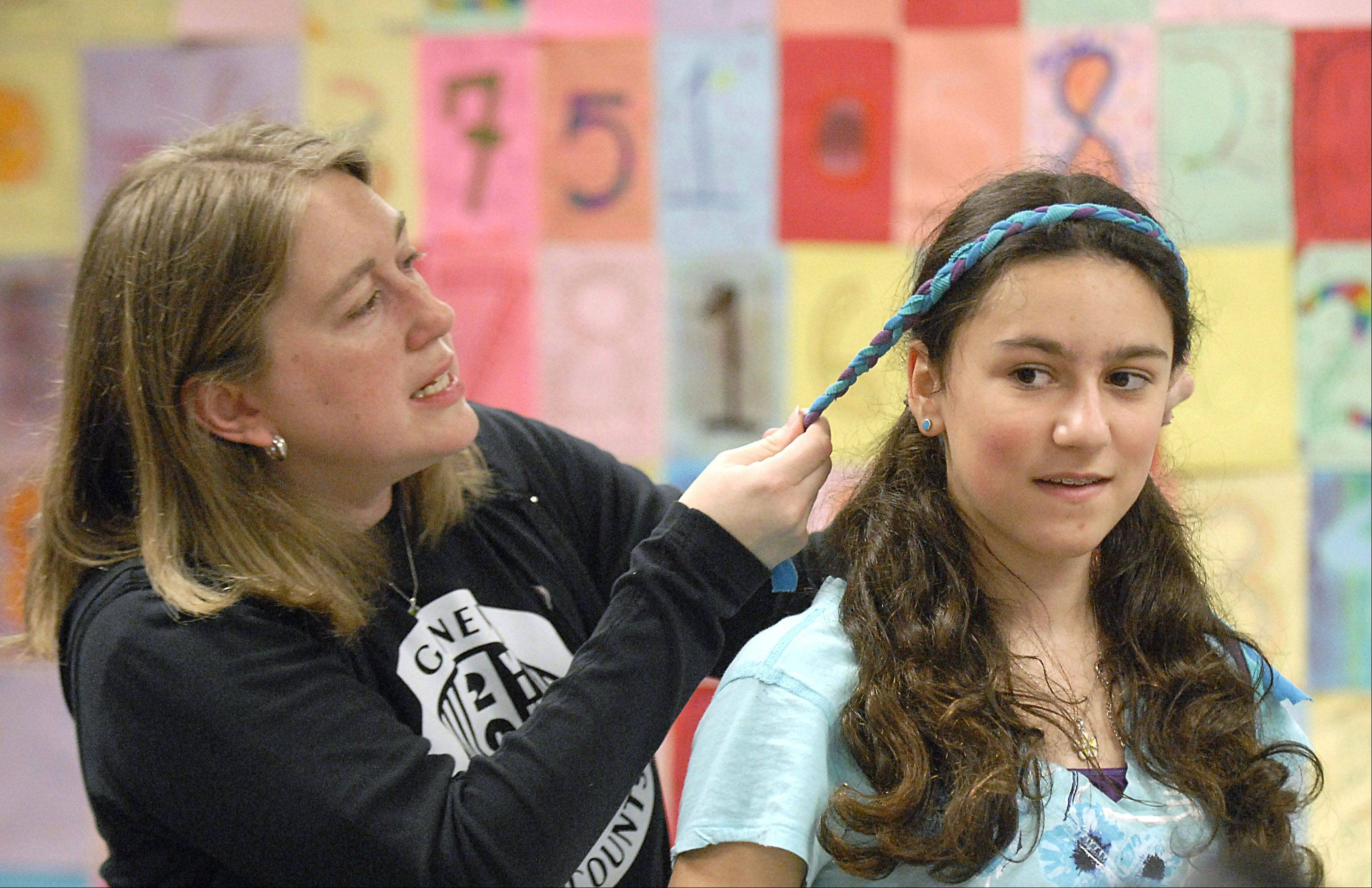 Seventh-grader Olivia Zieba, 12, gets help from teacher Kerry Gain to put on the headband she made from old T-shirts during Earth Day activities Friday at Geneva Middle School North. Students were given a few ideas of what to do with the shirts, but were encouraged to create freely.