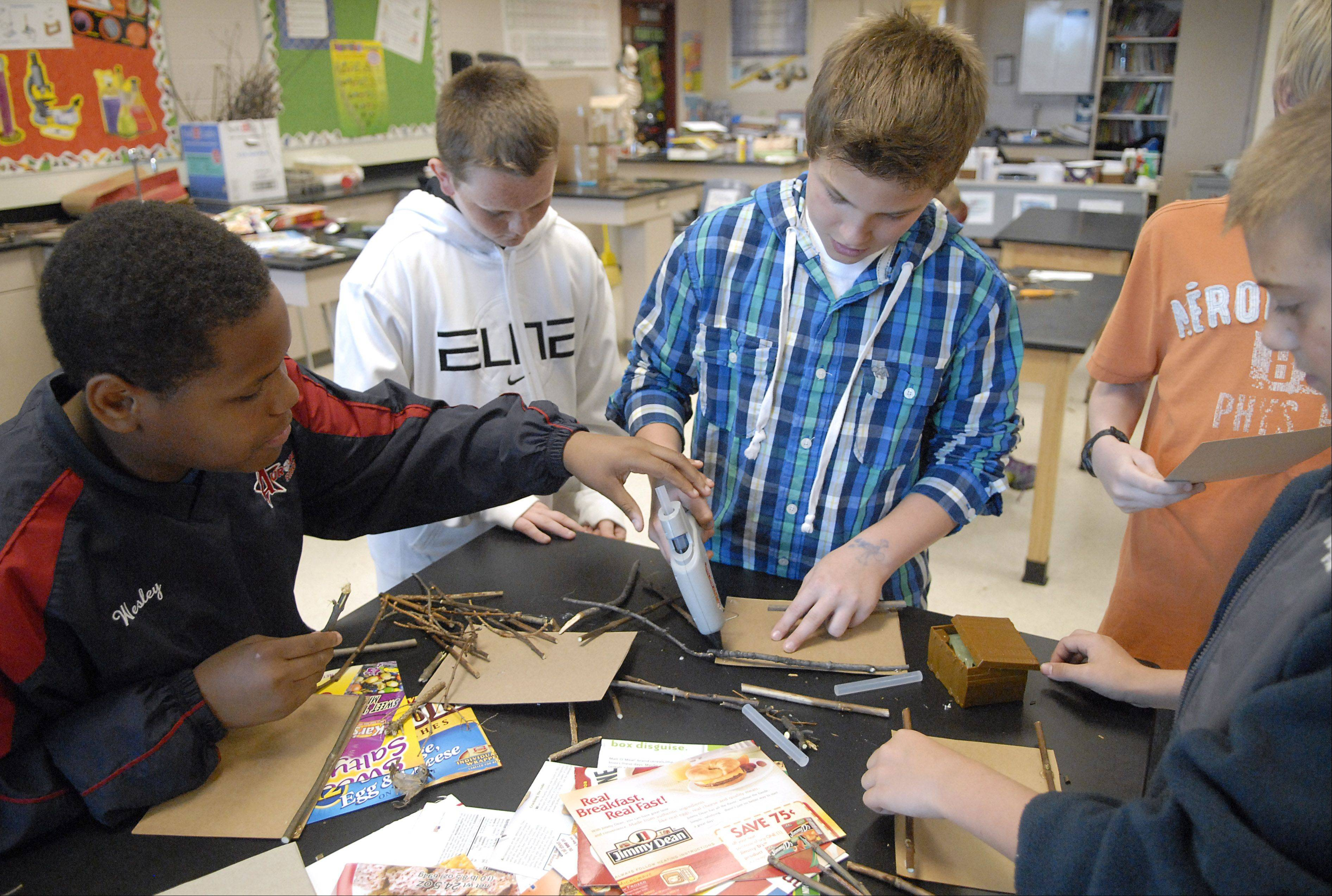 Prince Wesley, Kevin Huck, and Travis French, all 13, take turns using a hot glue gun to glue sticks onto cardboard to make a picture frame during their Earth Day celebration activities Friday at Geneva Middle School North.