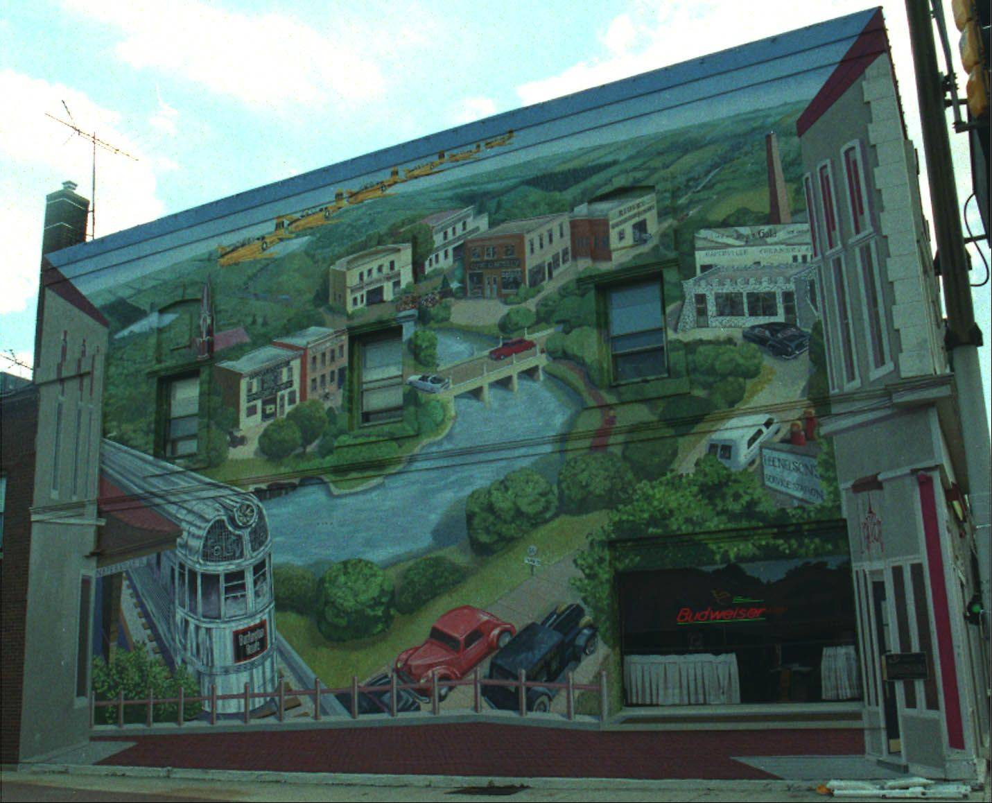 """A City in Transit"" by artists Mariah de Forest and Hector Duarte depicts the evolution of travel on the side wall of the Lantern Restaurant at the corner of Washington Street and Chicago Avenue in Naperville."