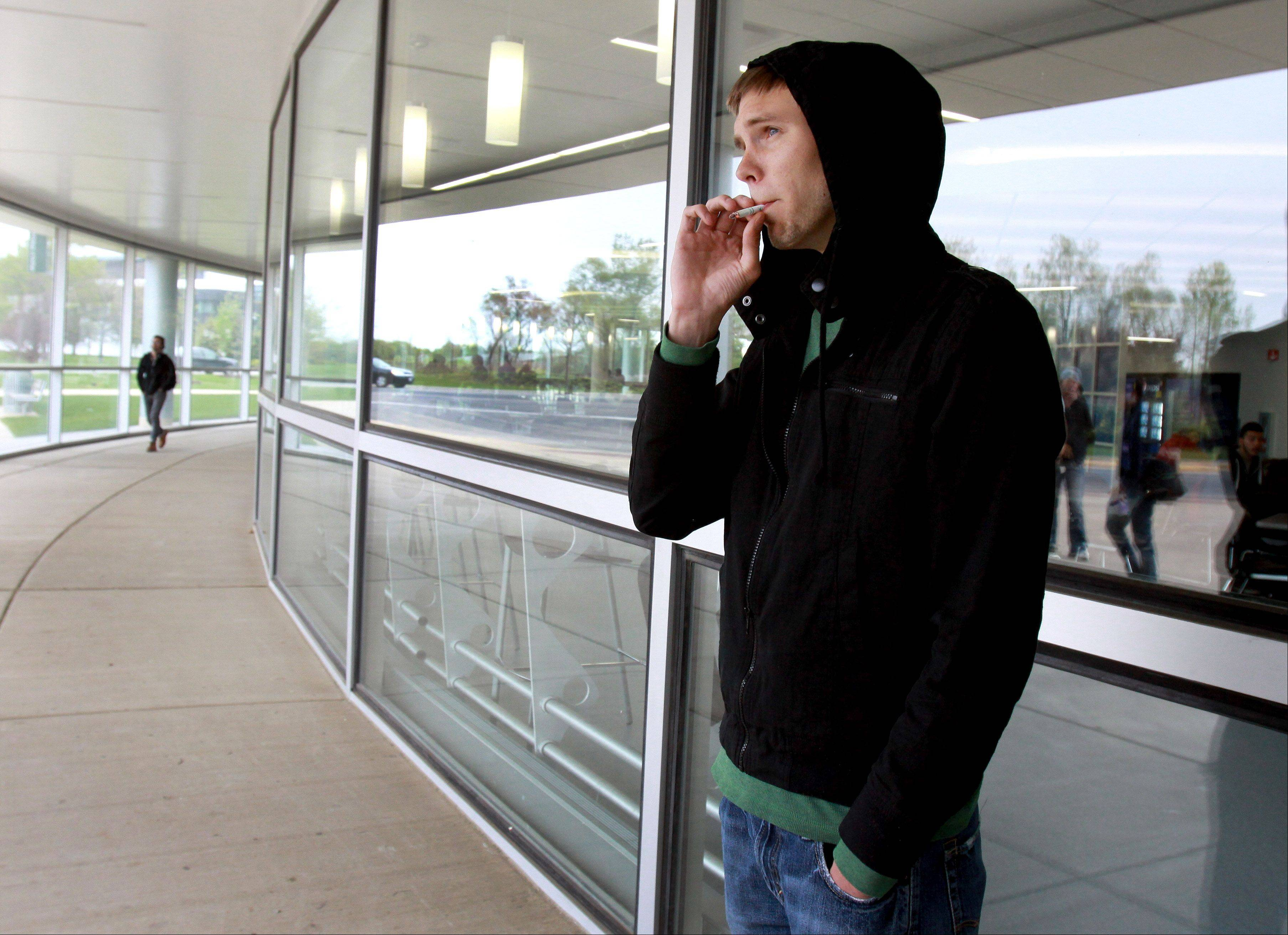 Robie Combs, a third-year student at College of DuPage, smokes outside the Student Resource Center on Friday. Combs says he's opposed to a collegewide smoking ban that goes into effect in August; instead he would have preferred designated smoking areas.