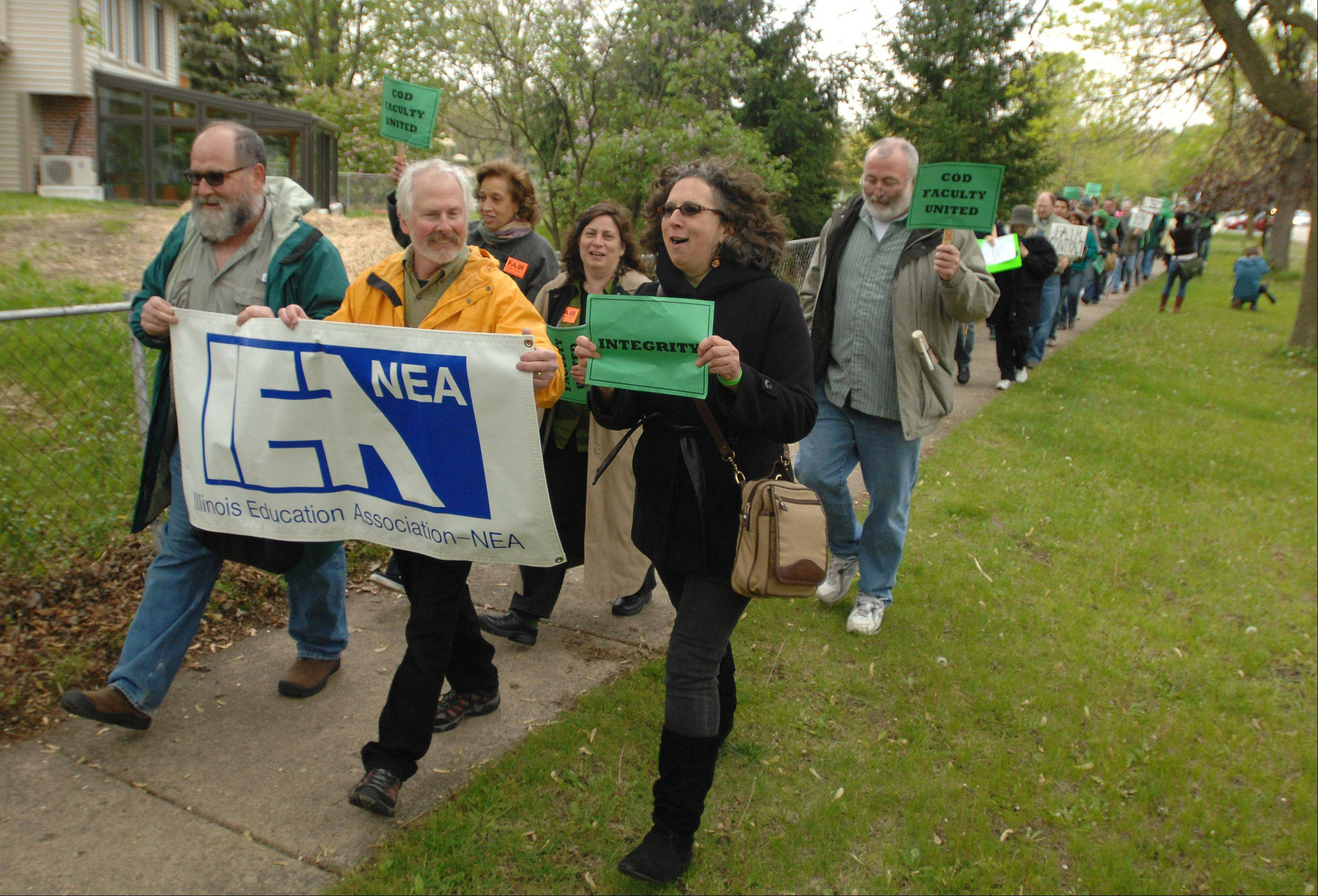 Members of the College of DuPage Faculty Association march down Lambert Road to call attention to stalled contract negotiations Thursday.