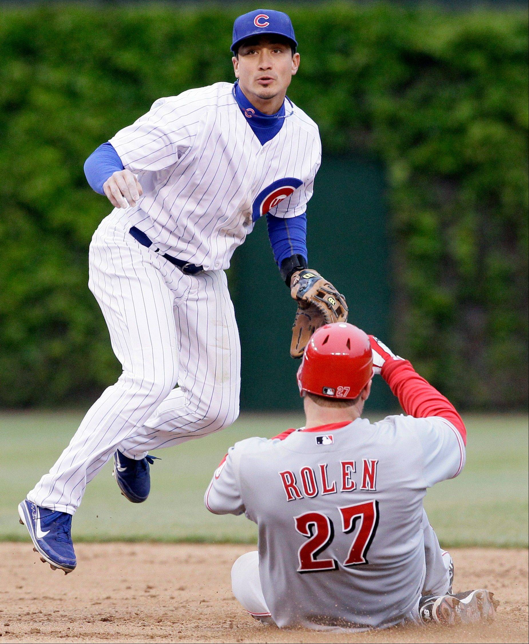 Cubs second baseman Darwin Barney, left, looks to first base after forcing out Cincinnati Reds' Scott Rolen at second base during the ninth inning of a baseball game in Chicago, Friday, April 20, 2012. Cincinnati Reds' Chris Heisey was out at first. The Reds won 9-4.