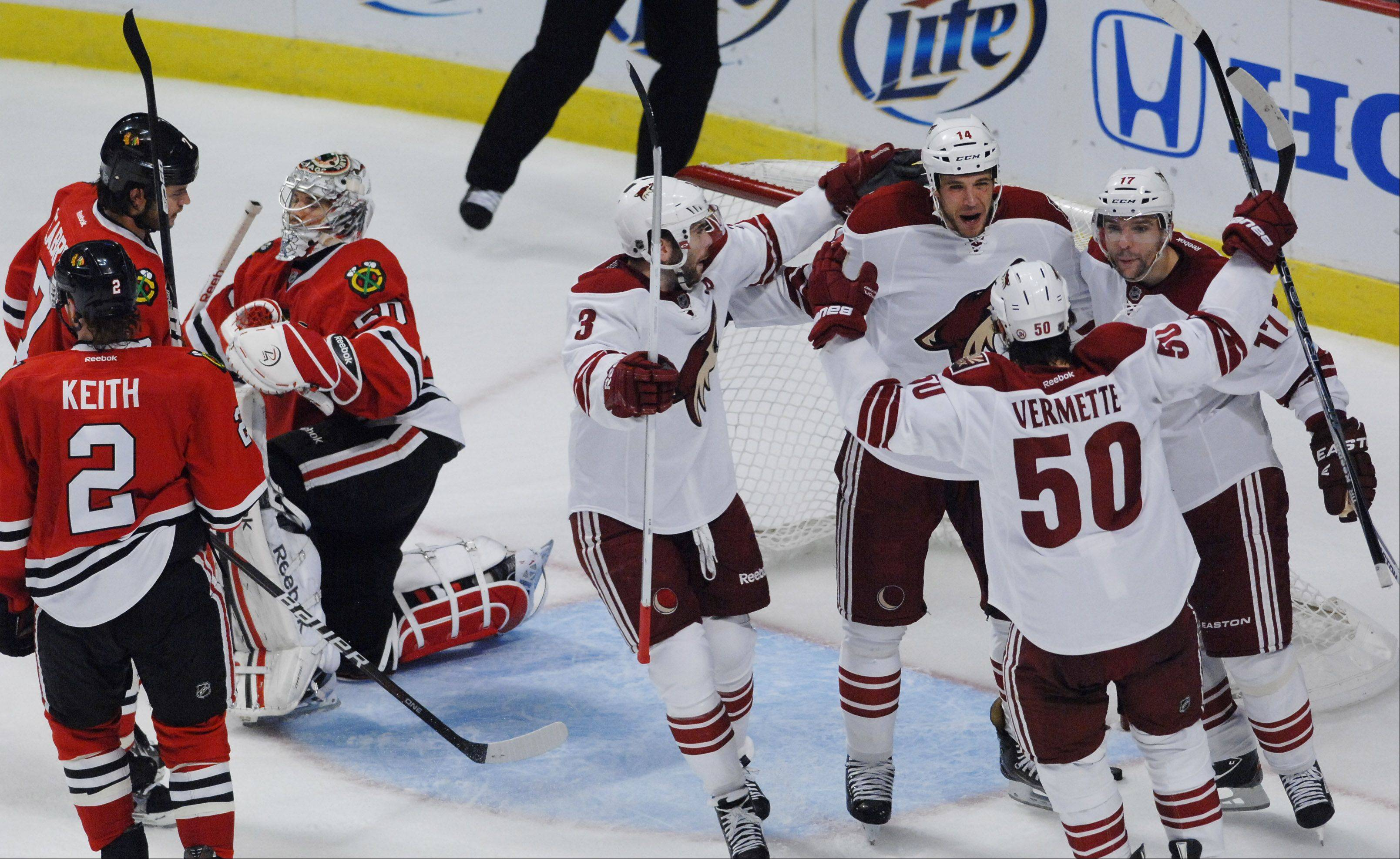 Chicago Blackhawks' goalie Corey Crawford and teammates react as Phoenix Coyotes celebrate a third-period goal.