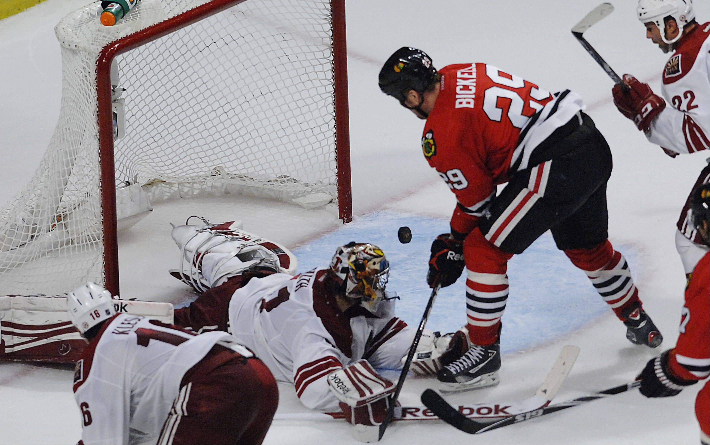Chicago Blackhawks' left wing Bryan Bickell tries to contain a loose puck in front of the net.