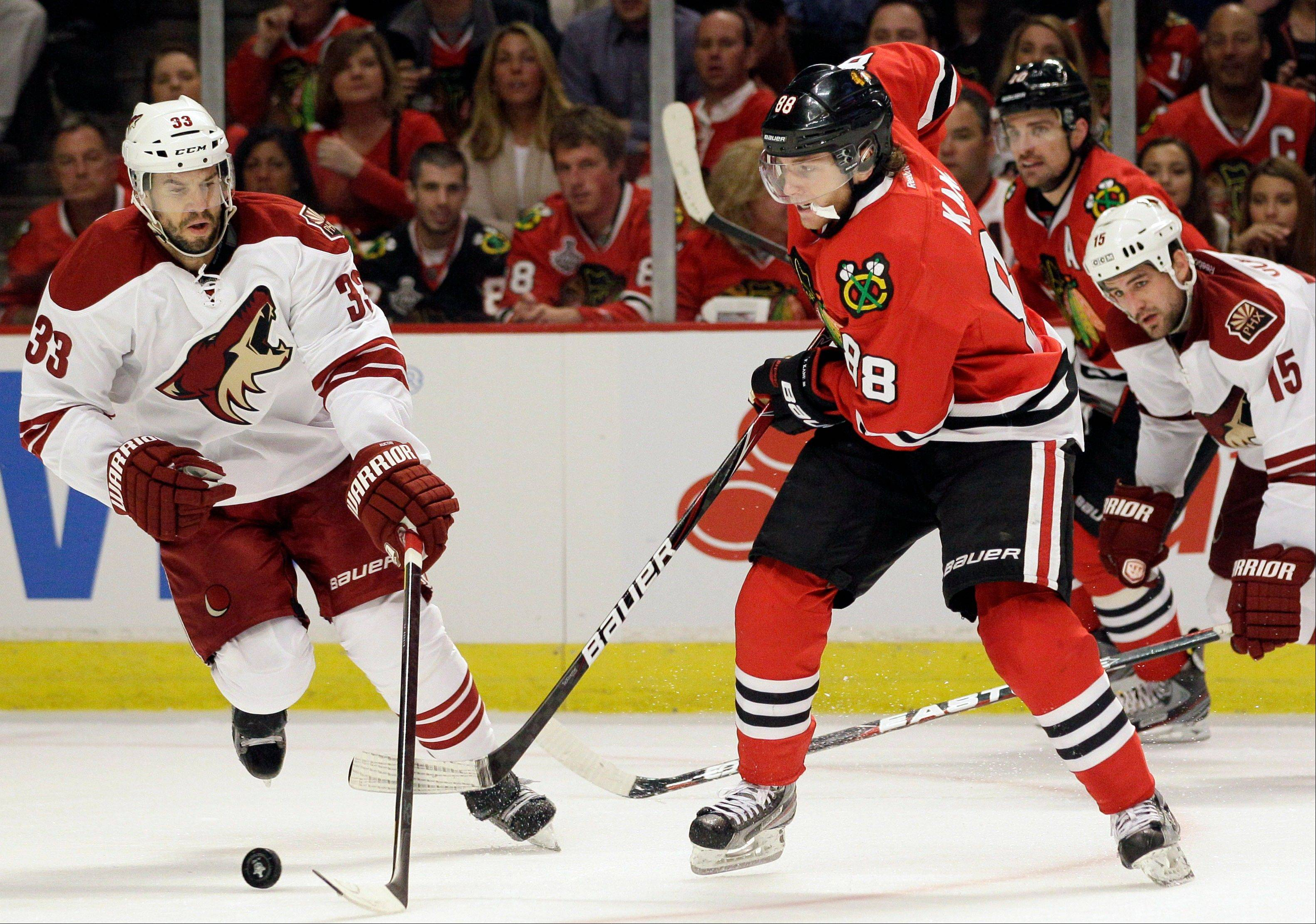 Chicago Blackhawks' Patrick Kane (88) passes the puck against Phoenix Coyotes' Adrian Aucoin (33) during the second period of Game 4 of an NHL hockey Stanley Cup first-round playoff series in Chicago, Thursday, April 19, 2012.