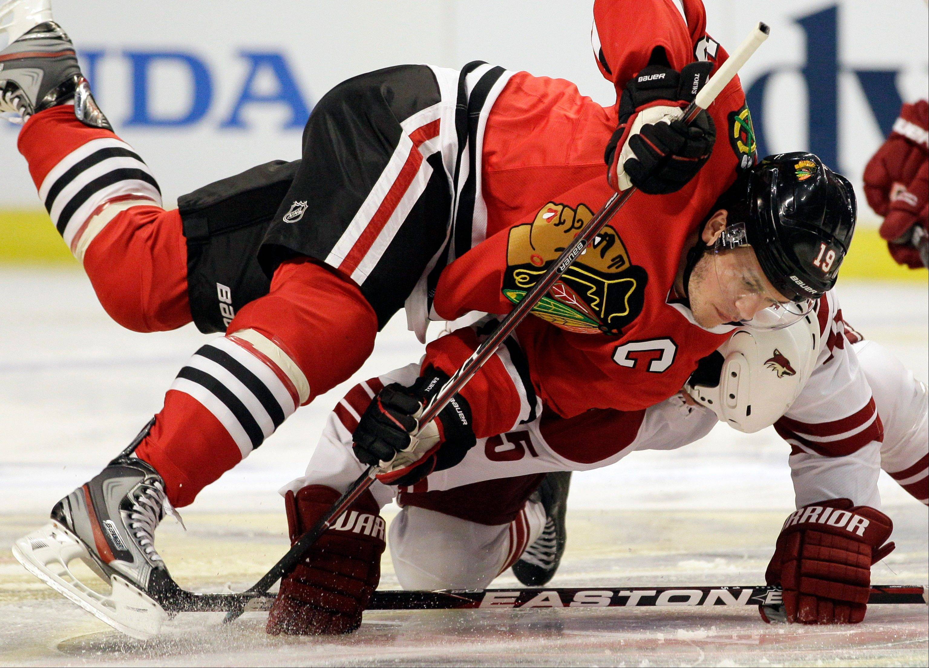 Chicago Blackhawks' Jonathan Toews (19) battles for the puck with Phoenix Coyotes' Boyd Gordon (15) during the first period of Game 4 of an NHL hockey Stanley Cup first-round playoff series in Chicago, Thursday, April 19, 2012.