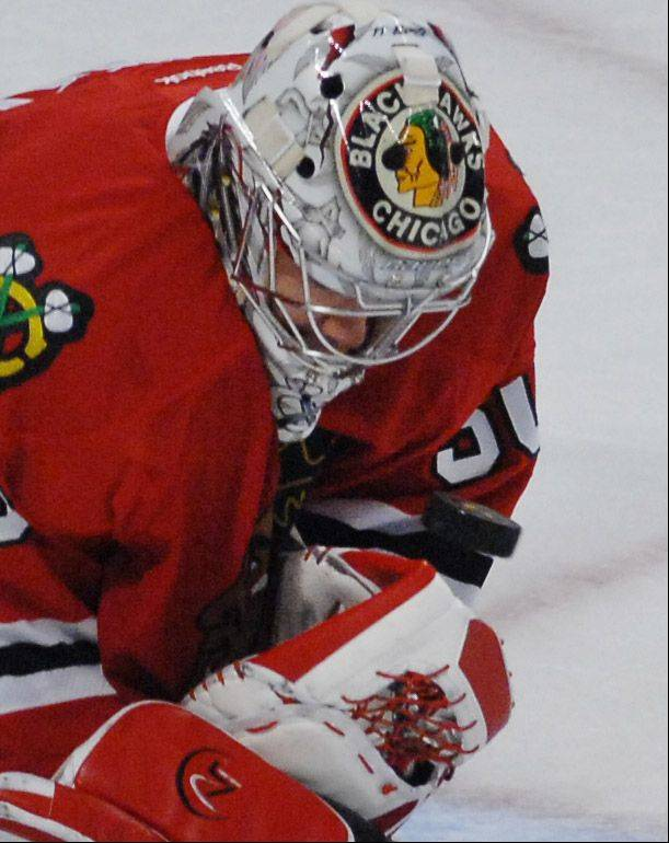 Chicago Blackhawks' goalie Corey Crawford stops a shot but loses the puck.
