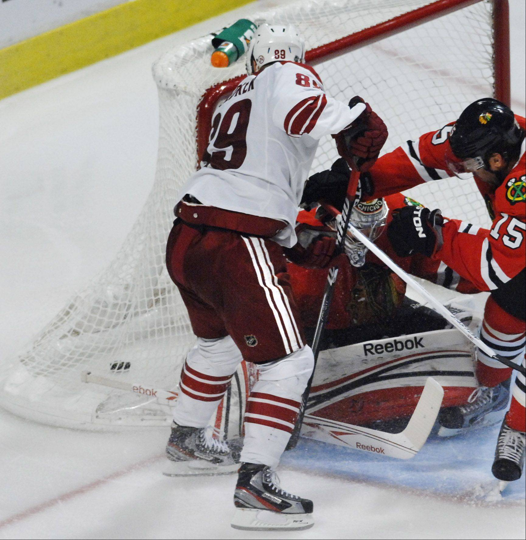Phoenix Coyotes' right wing Mikkel Boedker slips the puck in the net behind Chicago Blackhawks goalie Corey Crawford to win in overtime .