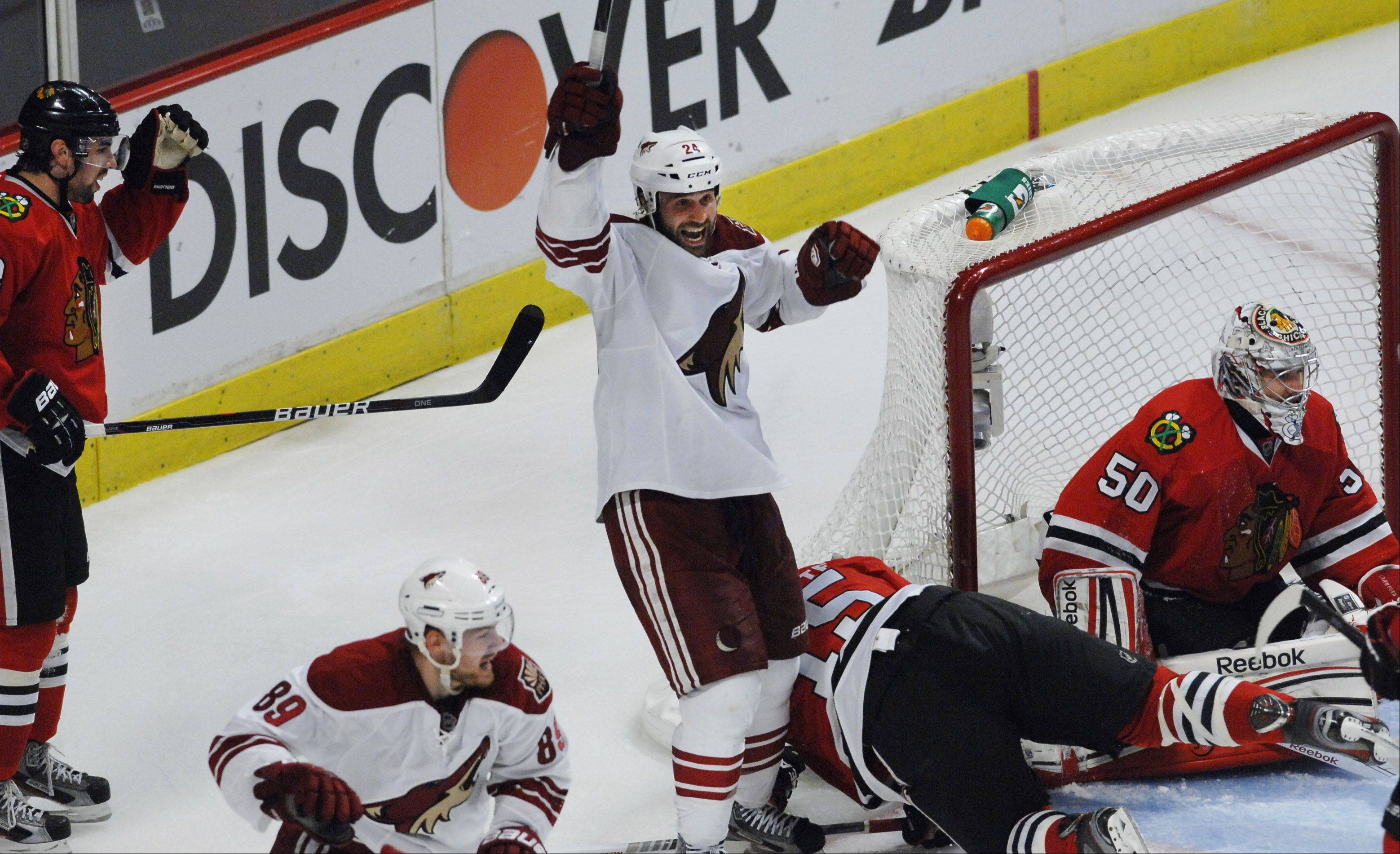 Phoenix Coyotes' center Kyle Chipchura celebrates teammate Mikkel Boedker's goal in overtime as Chicago Blackhawks' Nick Leddy, Andrew Brunette, and goalie Corey Crawford react.