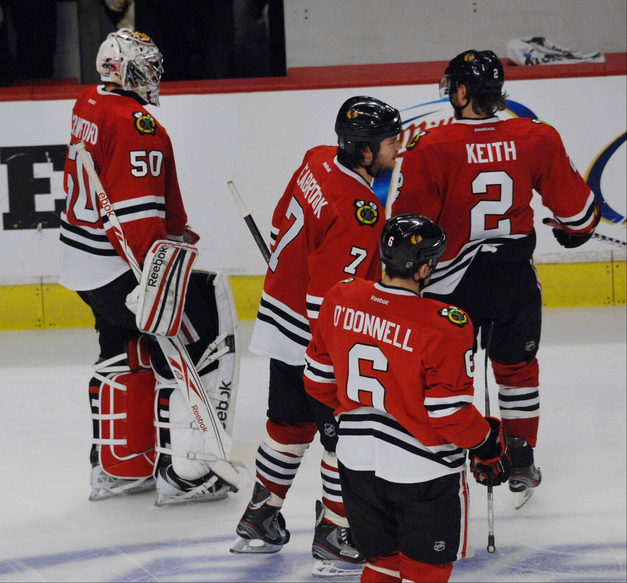 Chicago Blackhawks' goalie Corey Crawford leaves the ice with his teammates after losing in overtime.