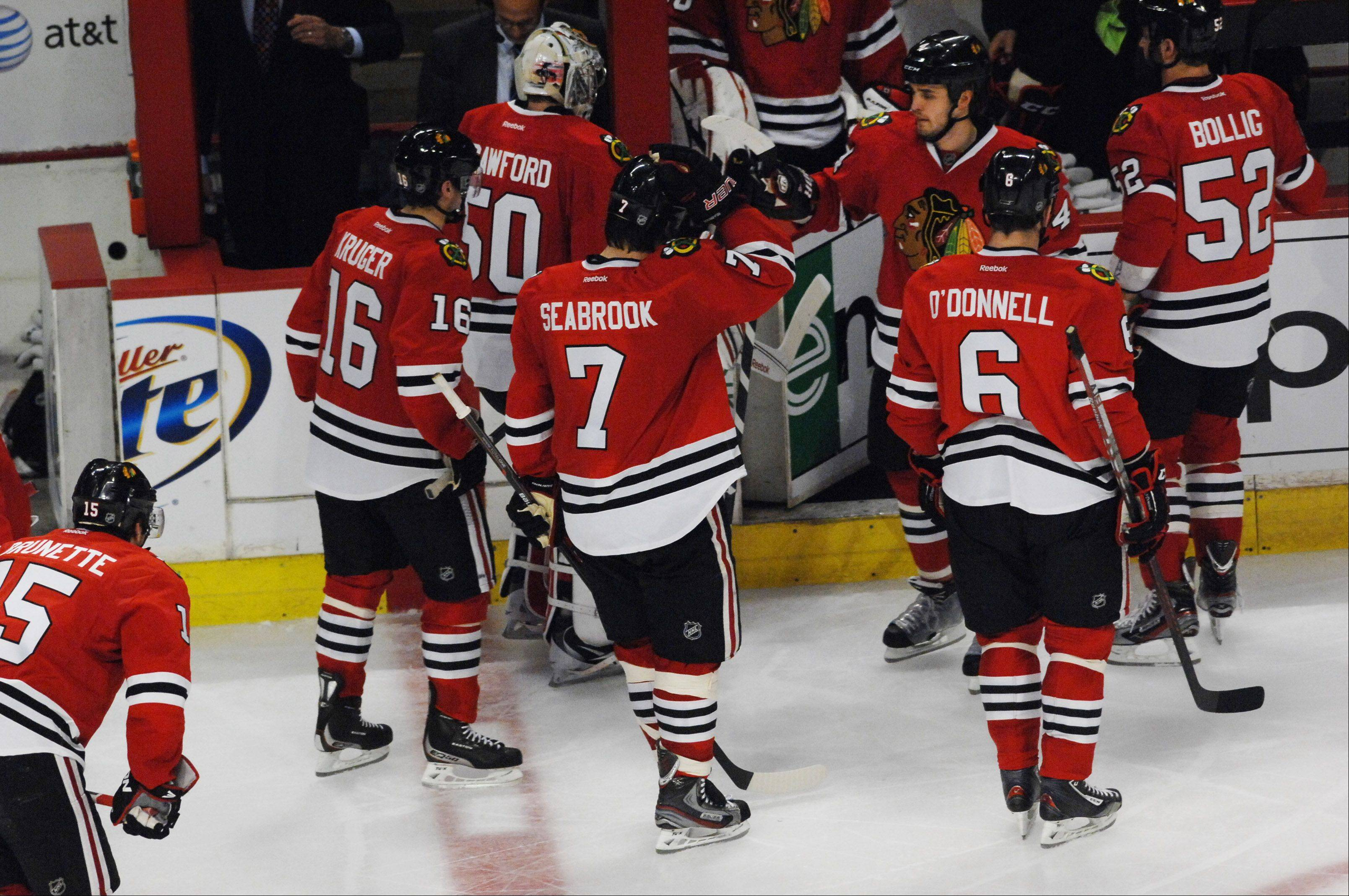 Chicago Blackhawks goalie Corey Crawford leaves the ice with his teammates after losing in overtime.