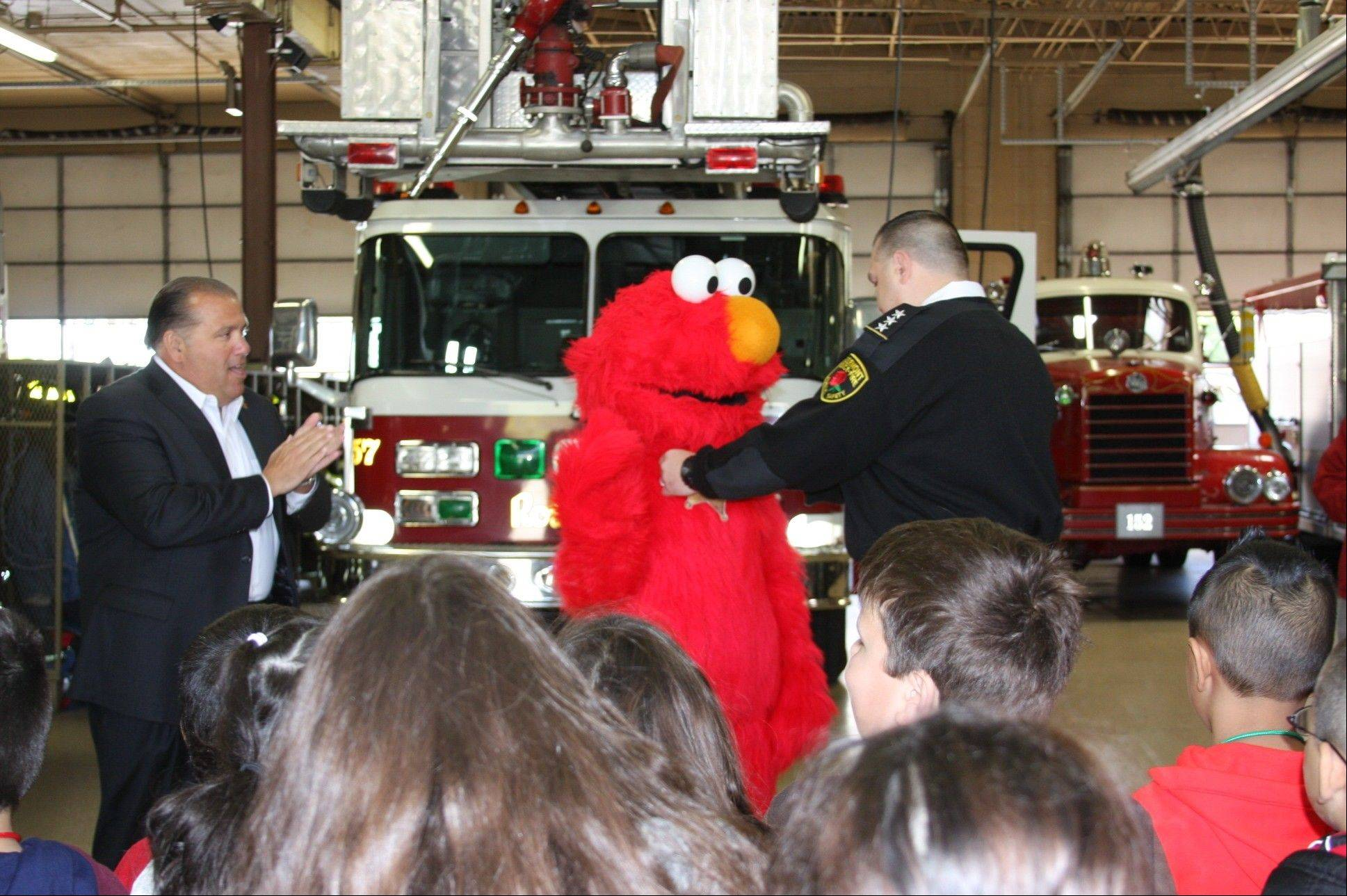 Mayor Brad Stephens and Rosemont Chief of Public Safety Donald Stephens III make Elmo deputy for the day.