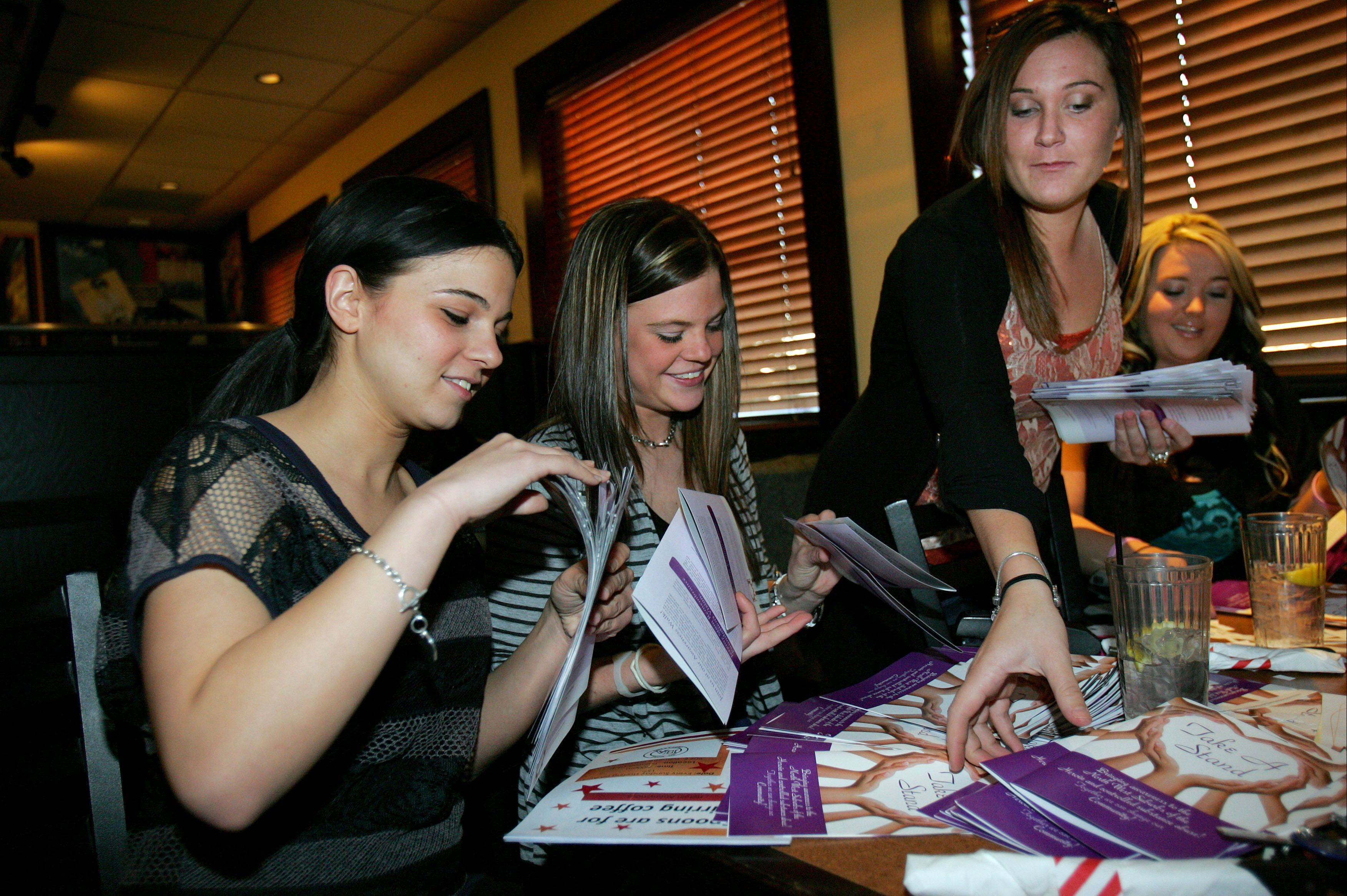 Take A Stand founders, from left, Lindsey Dulian, Megan Hartigan, Shannon Brody and Heather Riley organize stacks of their brochures in Lake Zurich.