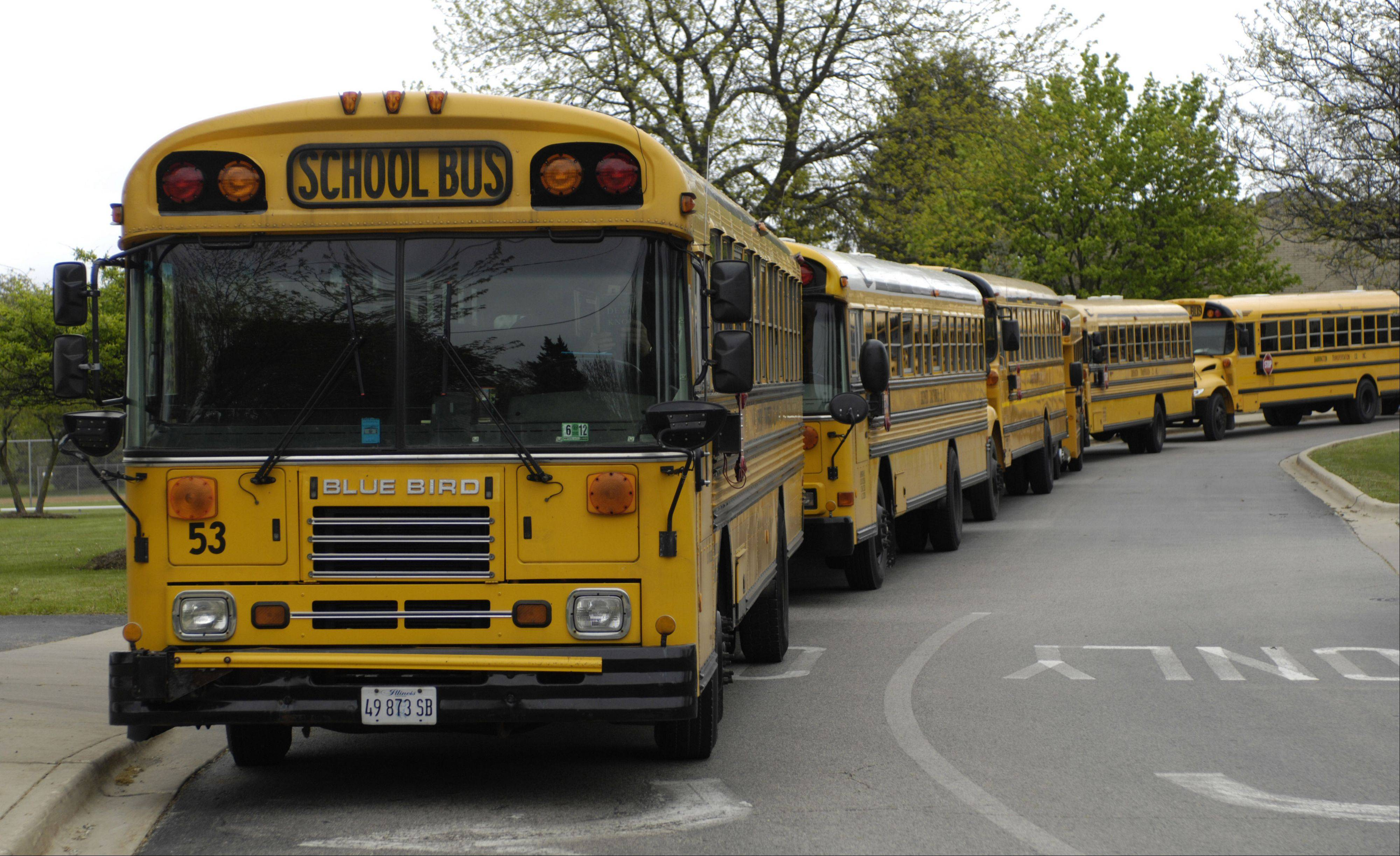 Buses line up before dismissal at Barrington Middle School Station campus Friday. Illinois is considering letting schools charge fees for busing students.