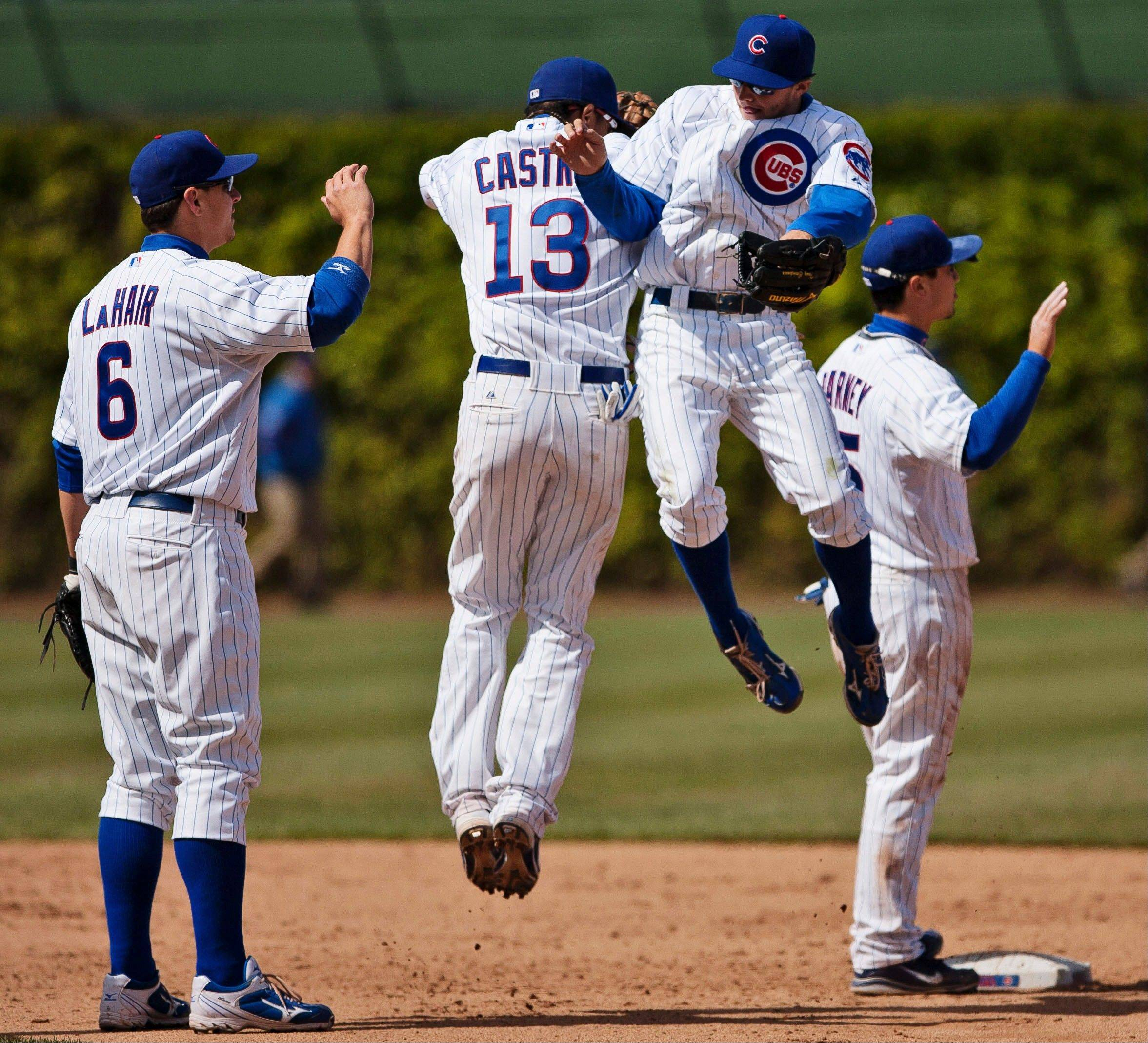 Chicago Cubs' Starlin Castro (13) and Tony Campana leap into each other as they celebrate with Bryan LaHair after defeating the Cincinnati Reds 6-1 Saturday at Wrigley Field.
