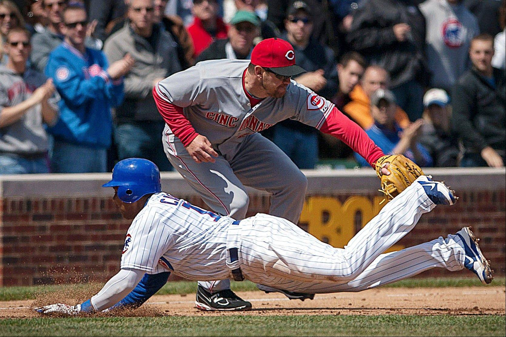 Starlin Castro of the Cubs slides past Cincinnati Reds third baseman Scott Rolen after hitting a triple during the second inning Saturday at Wrigley Field