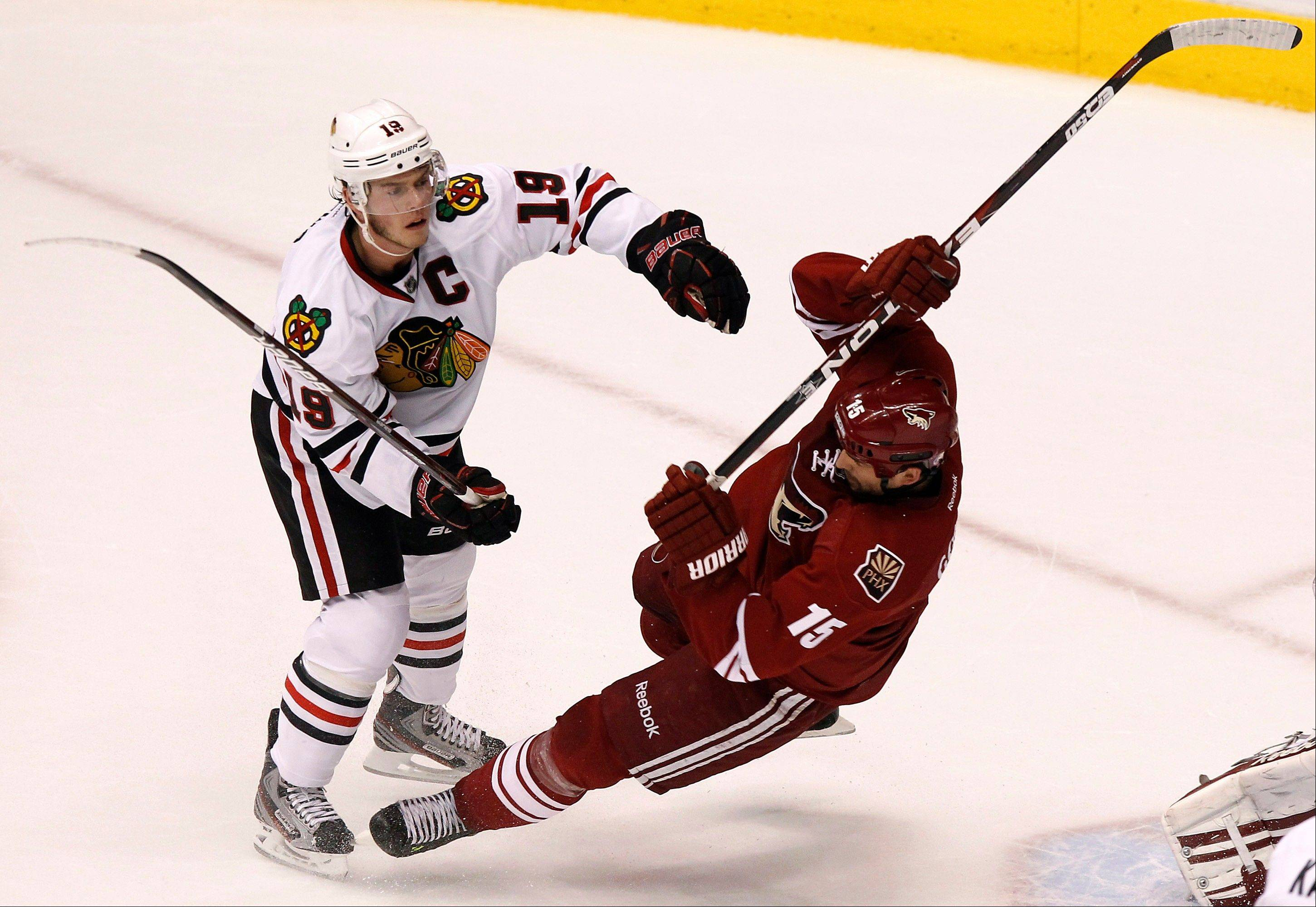 Jonathan Toews (19) checks Phoenix Coyotes' Boyd Gordon (15) to the ice during the first period in Game 5 of an NHL hockey Stanley Cup first-round playoff series Saturday, April 21, 2012, in Glendale, Ariz.