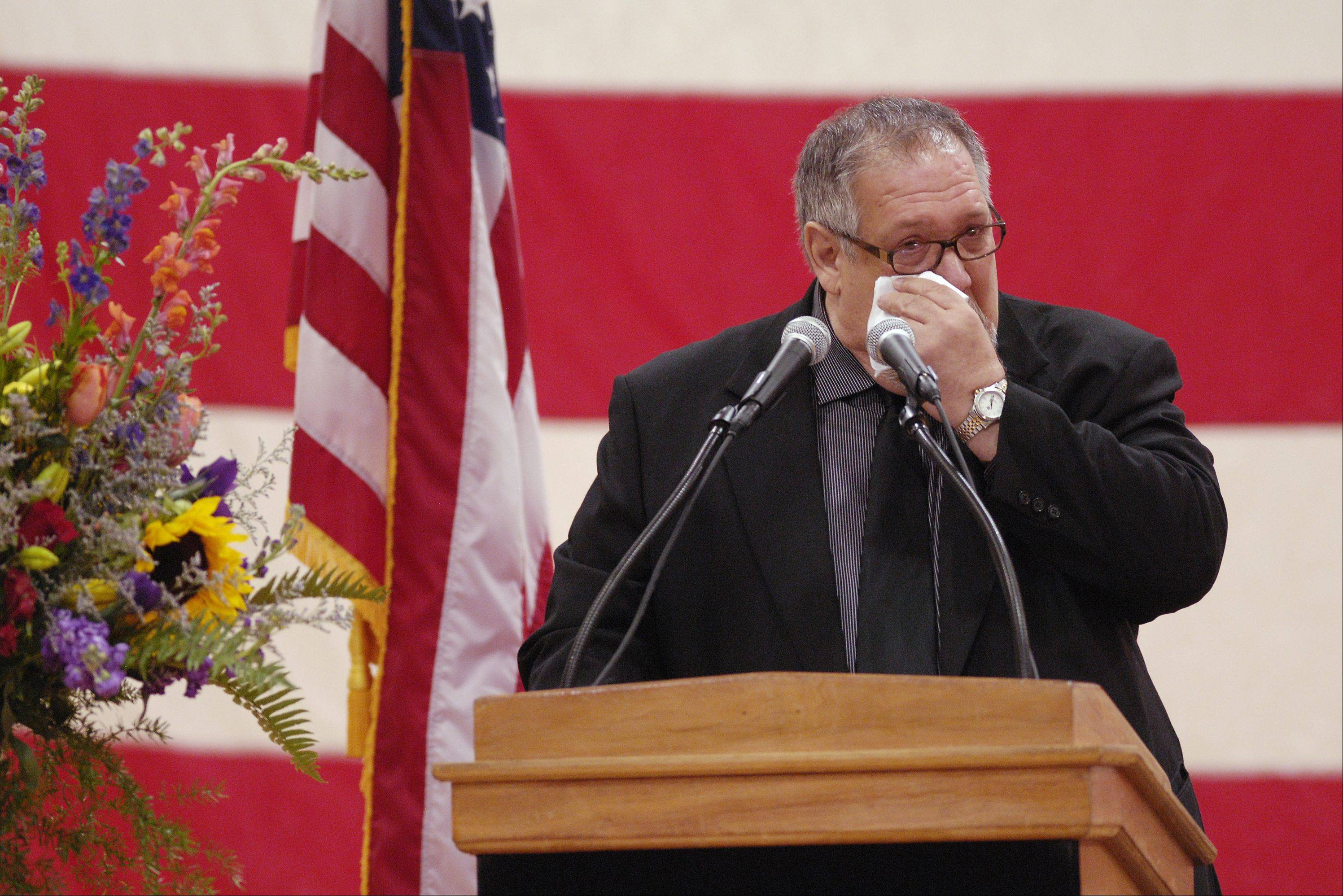 Steve Kwasman wipes a tear from his eye Sunday as he speaks during the memorial service for brother, West Chicago Mayor Mike Kwasman, at West Chicago High School.