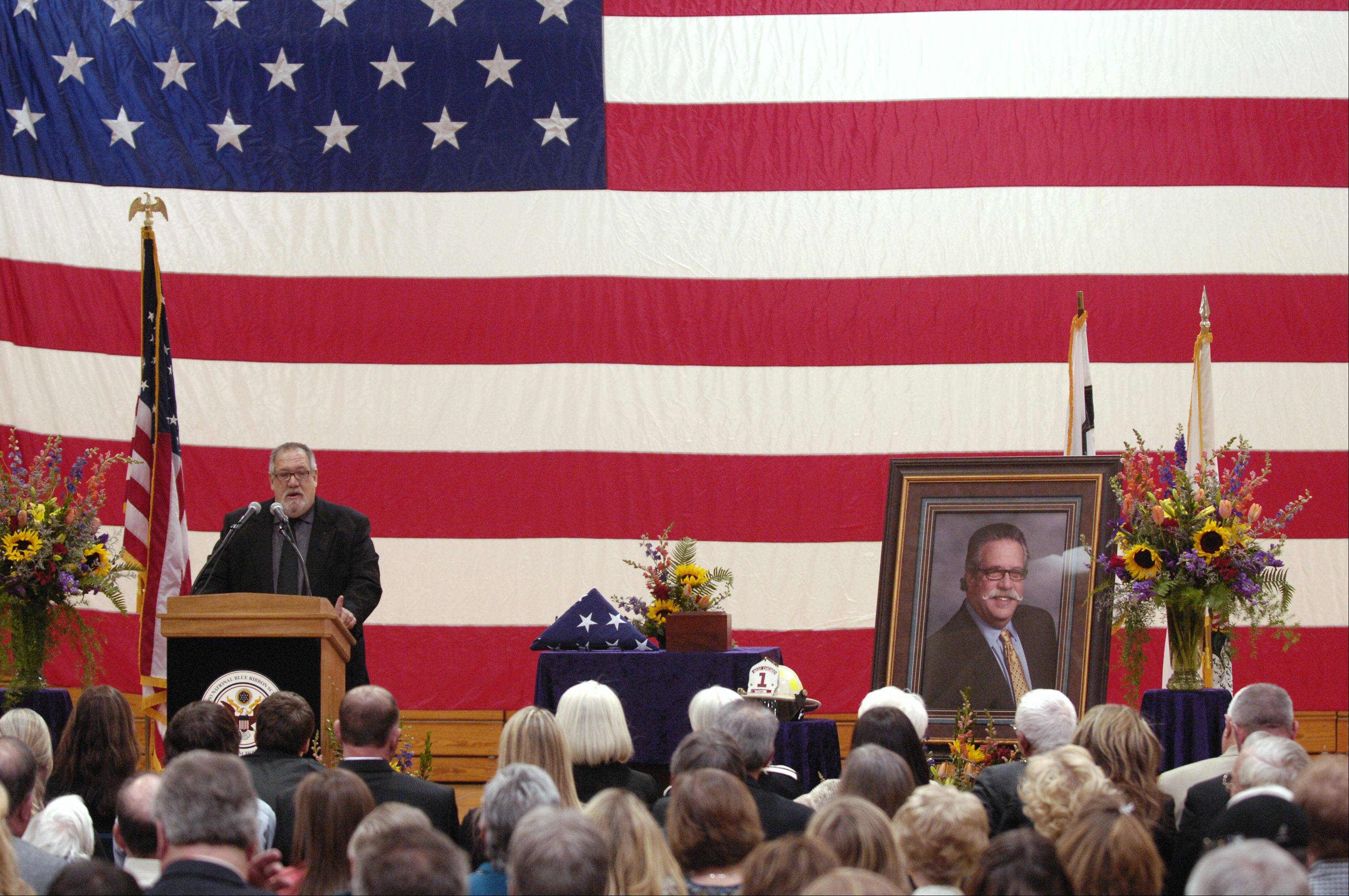 Steve Kwasman speaks Sunday during the memorial service for brother, West Chicago Mayor Mike Kwasman, at West Chicago High School.