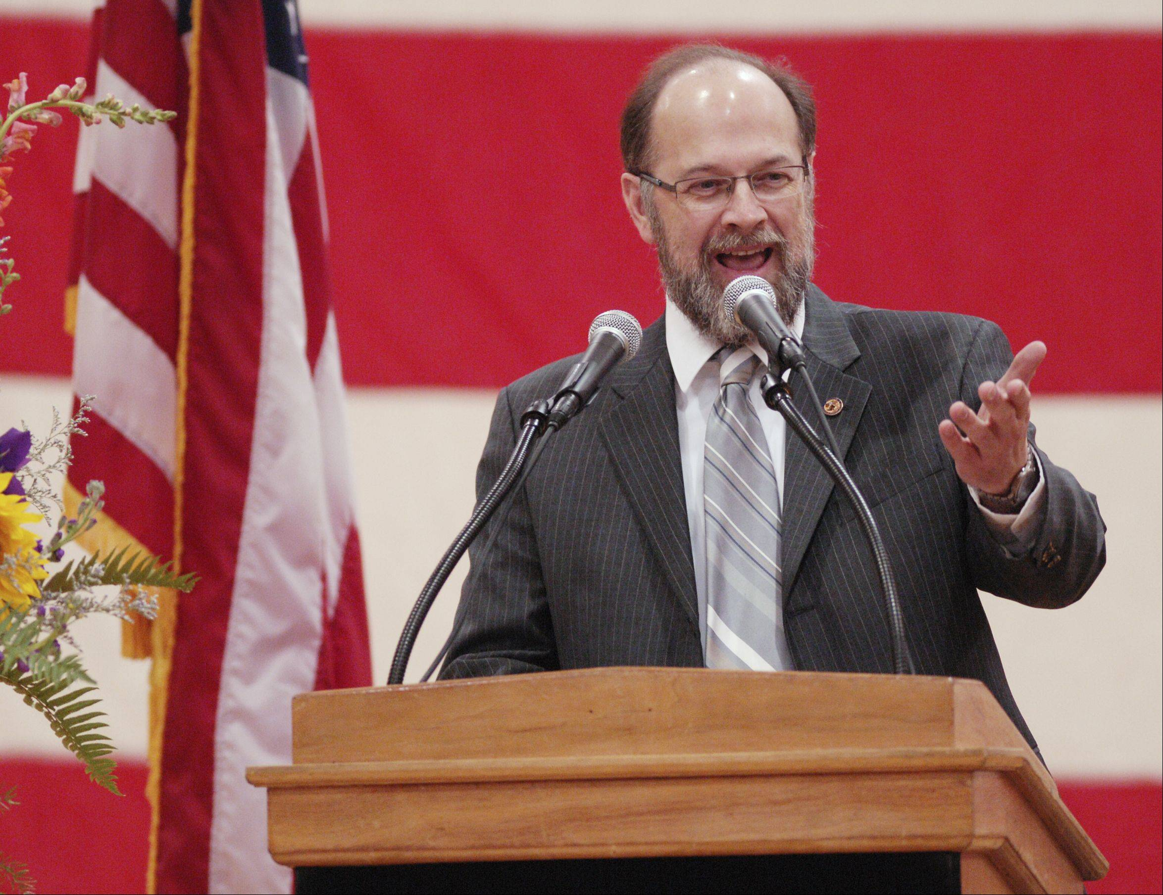 Mike Fortner, state representative and former mayor, speaks Sunday at the memorial service for West Chicago Mayor Mike Kwasman at West Chicago High School.